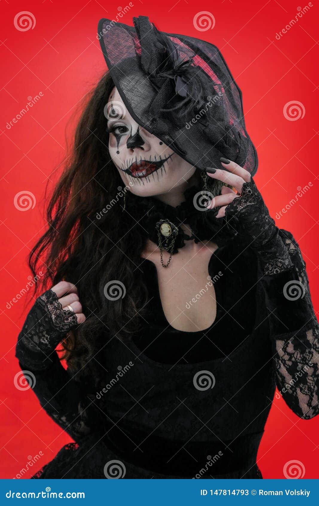 Портрет молодого брюнета с макияжем в стиле хеллоуина в черных одеждах и шляпе Ужасная девушка со страшным ртом и