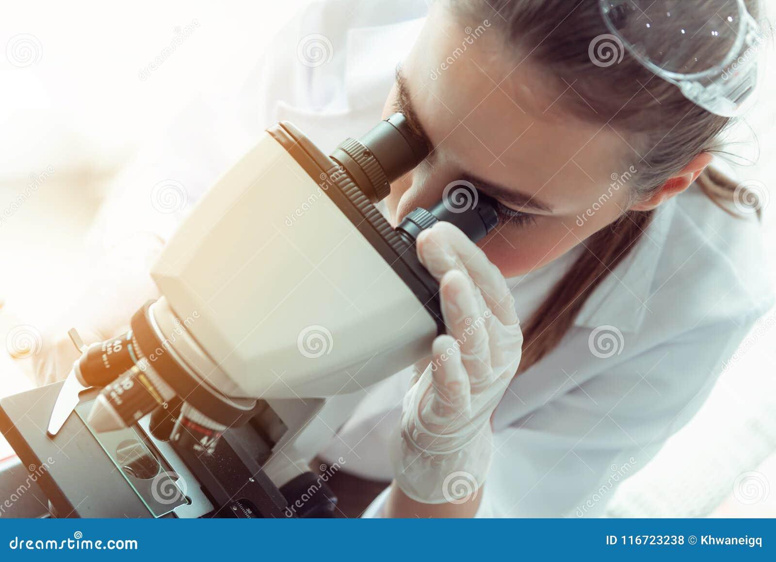 Портрет молодого исследования ученого используя микроскоп в работе