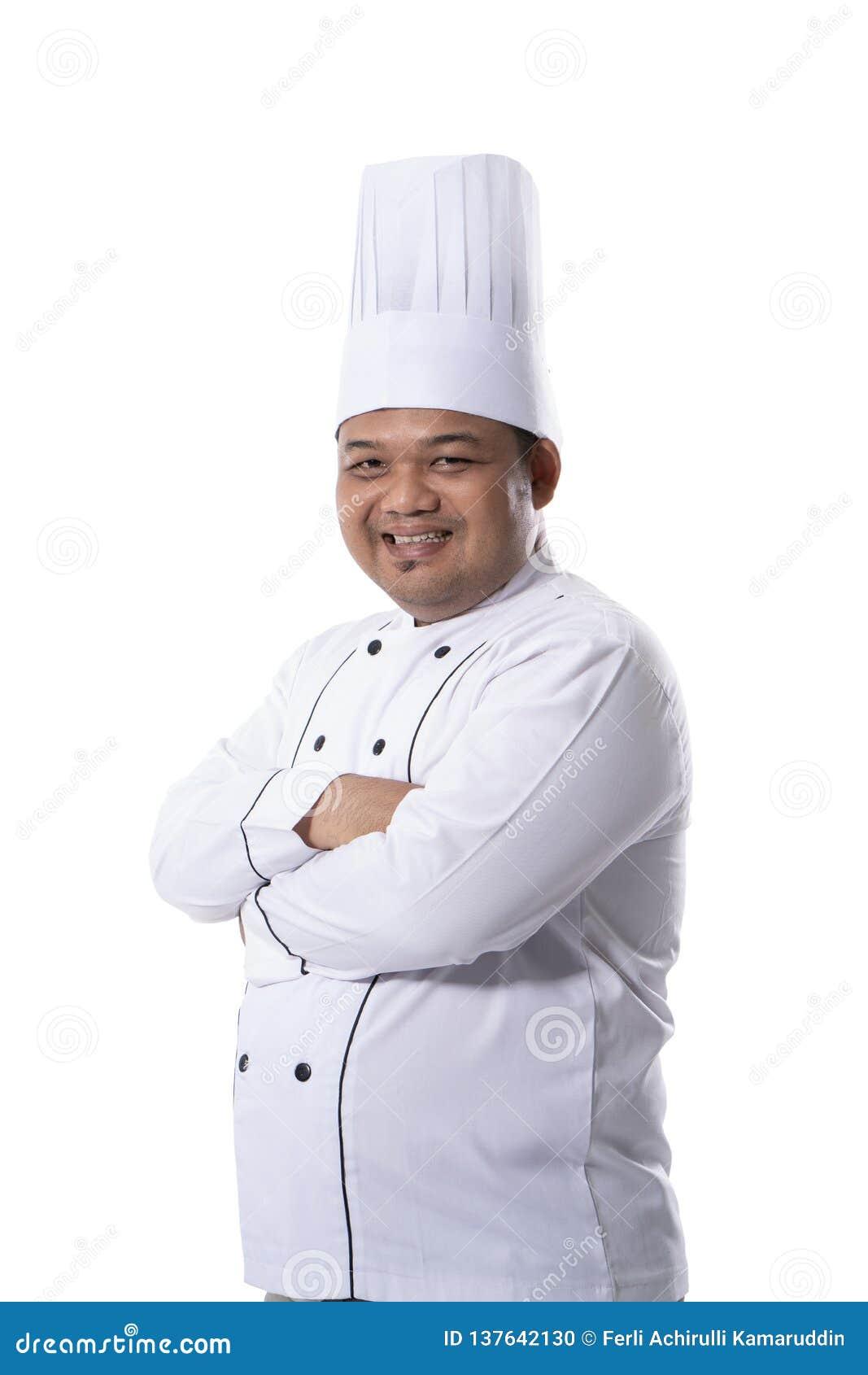 Портрет молодого мужского шеф-повара стоя уверенные пересеченные руки представляет взгляд на фронте камеры