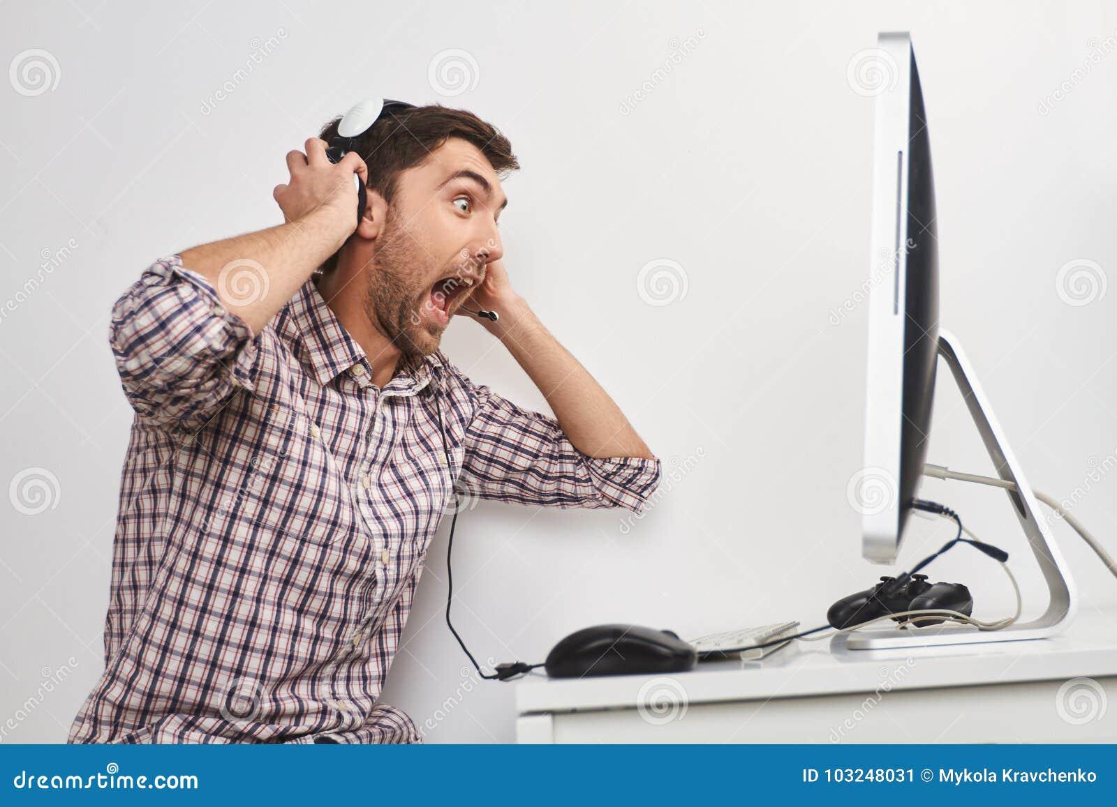 Портрет молодого смешного бородатого мужского gamer в checkered рубашке играя игры на персональном компьютере, нося наушники