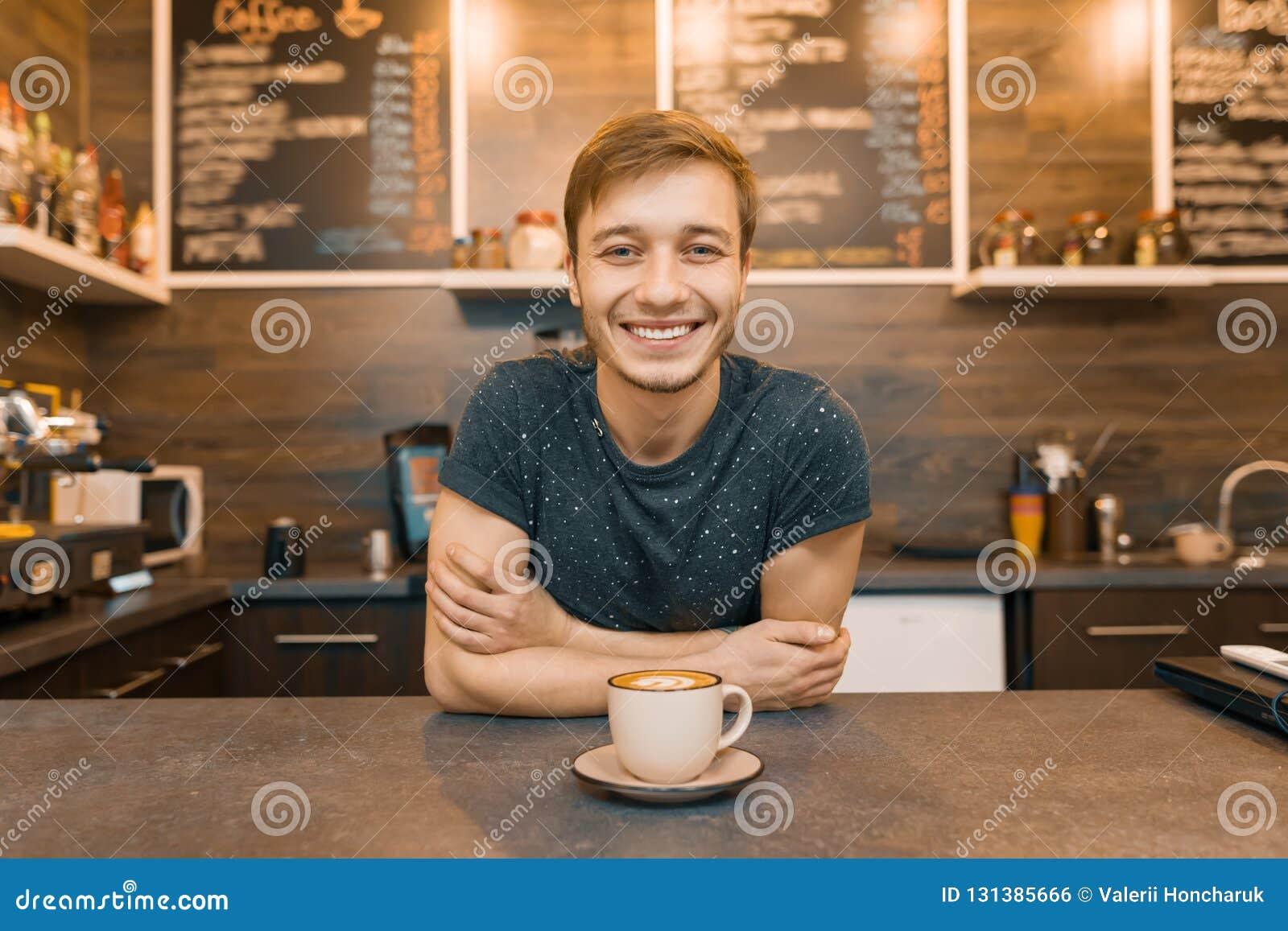 Портрет молодого усмехаясь мужского barista с подготовленным напитком с оружиями пересек стоять за счетчиком кафа Дело co кофейни