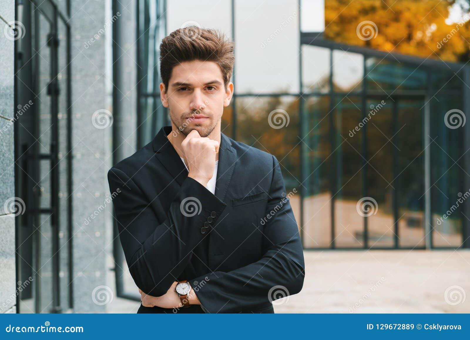 Портрет молодого успешного задумчивого бизнесмена в городе Человек в куртке дела на предпосылке офисного здания красиво
