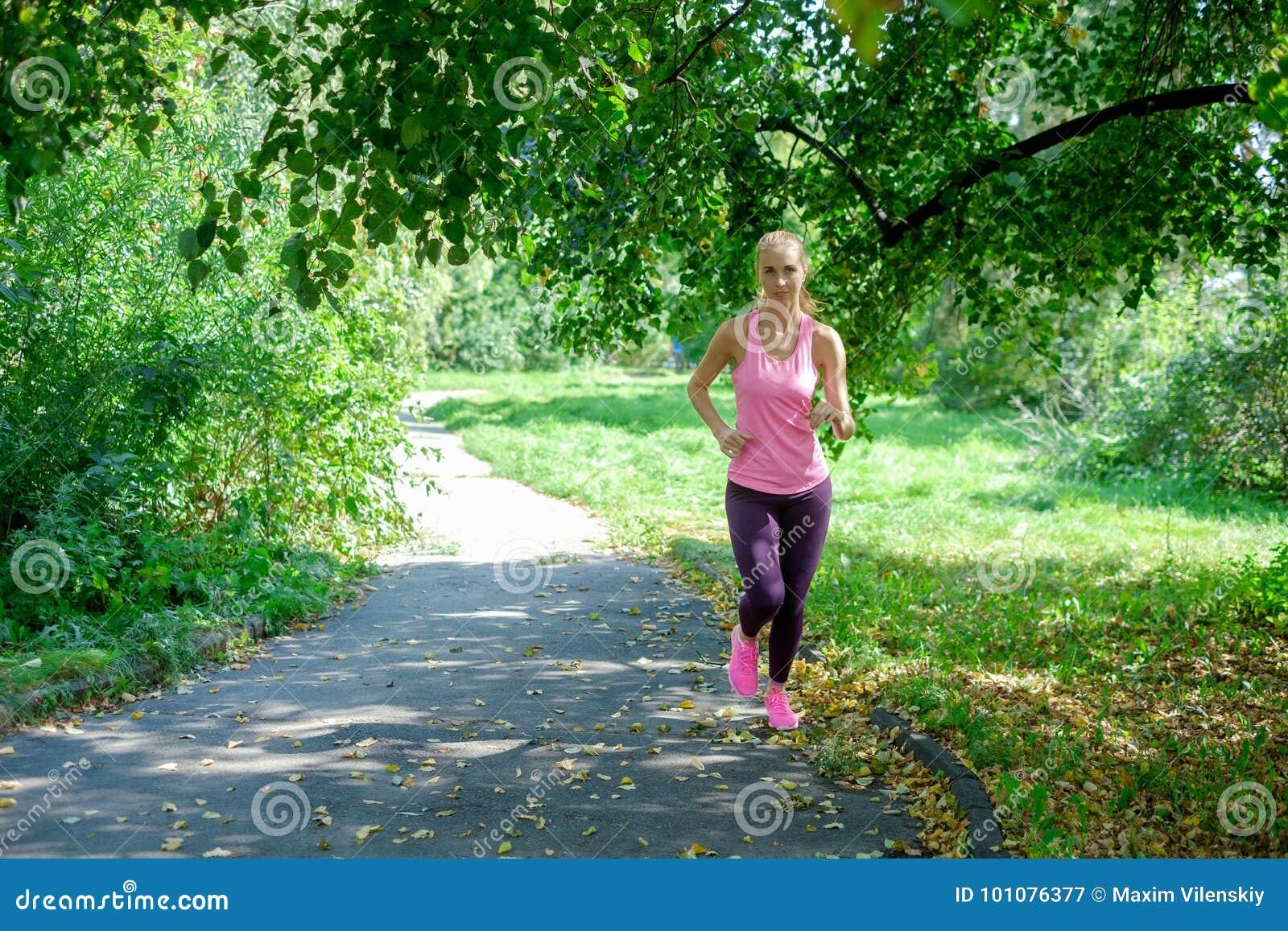 Портрет молодой женщины бежать самостоятельно в парке