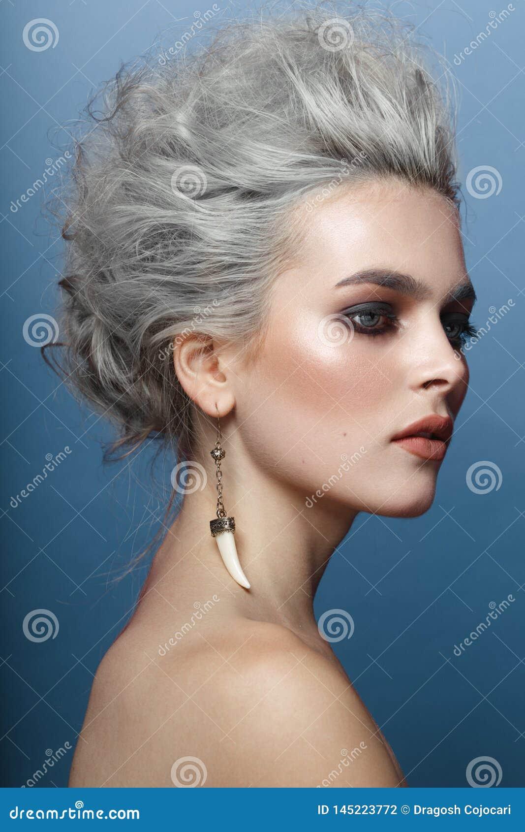 Портрет молодой женщины с серыми стилем причесок, глазами smokey и макияжем с нагими плечами, изолированными на голубой предпосыл