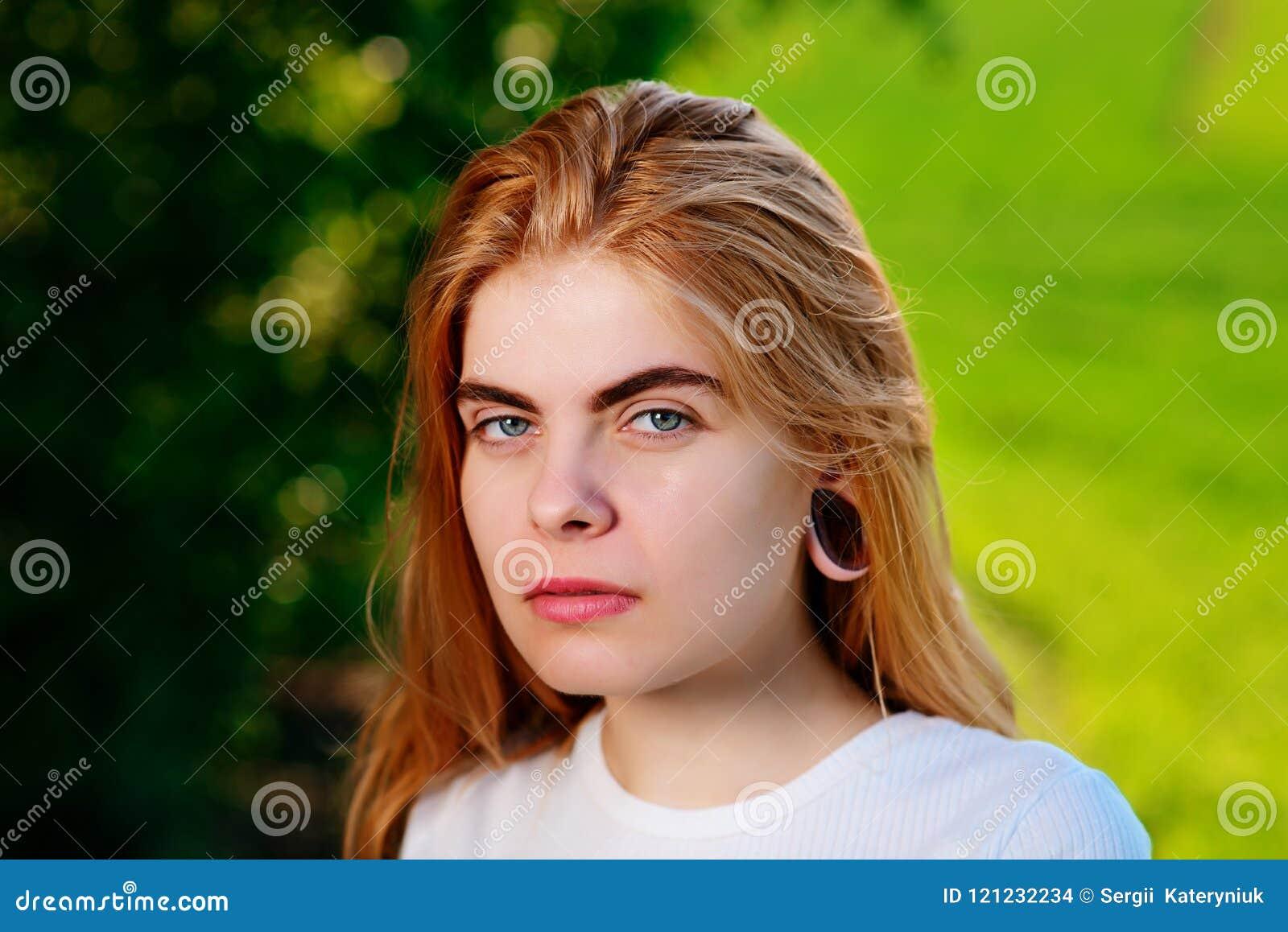 Портрет молодой красивой женщины с деревянными тоннелями в ее e