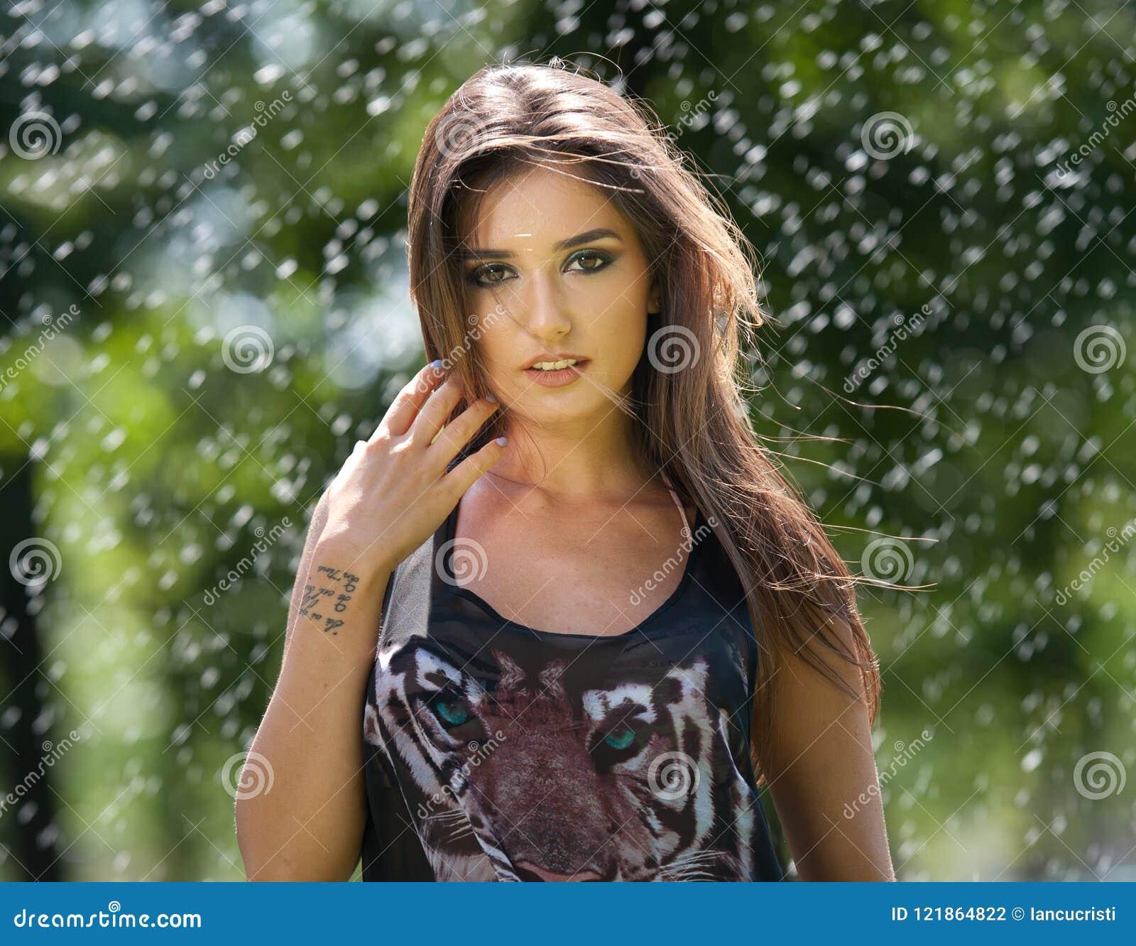 Портрет молодой сексуальной женщины в брызге воды Красивые девушки с длинными ногами и улыбками Счастливая молодая женщина в парк