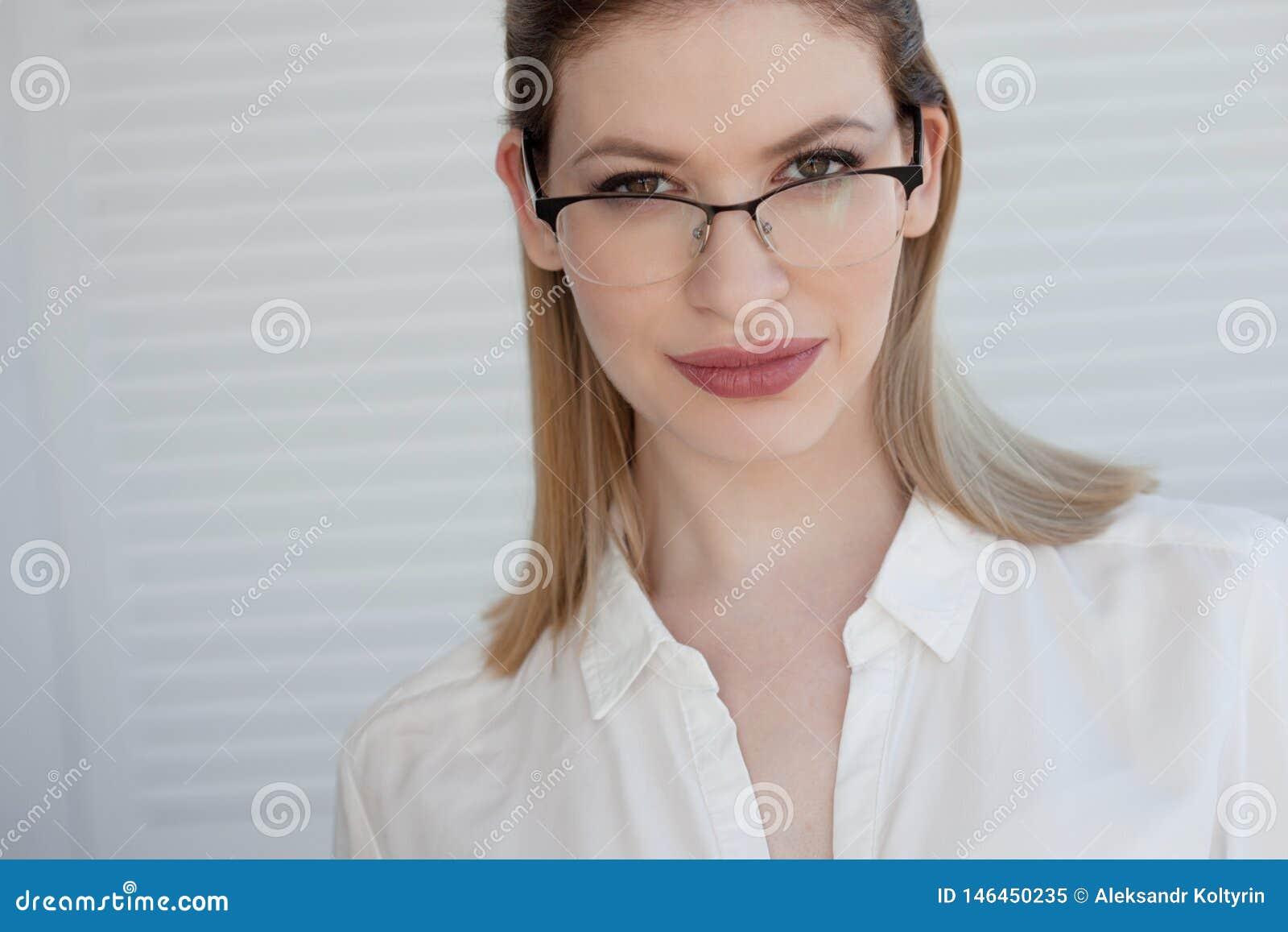 Портрет молодой стильной бизнес-леди в белой рубашке и стеклах