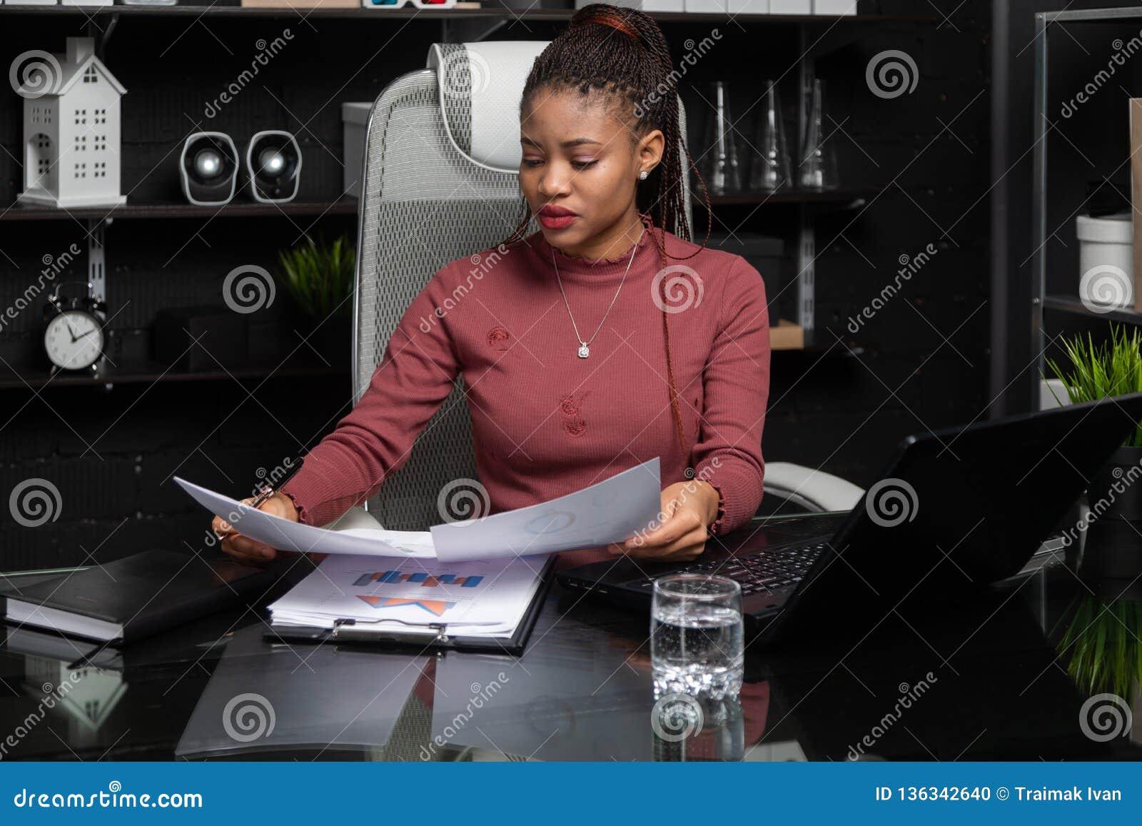 Портрет молодой черной коммерсантки работая с диаграммами и диаграммами на столе в офисе