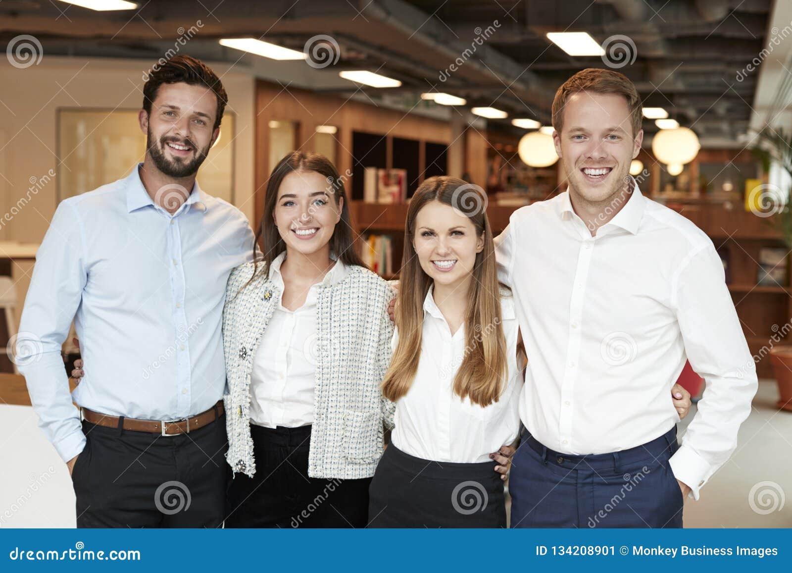 Портрет молодых бизнесменов и коммерсанток стоя в современном офисе на постдипломном дне оценки рекрутства