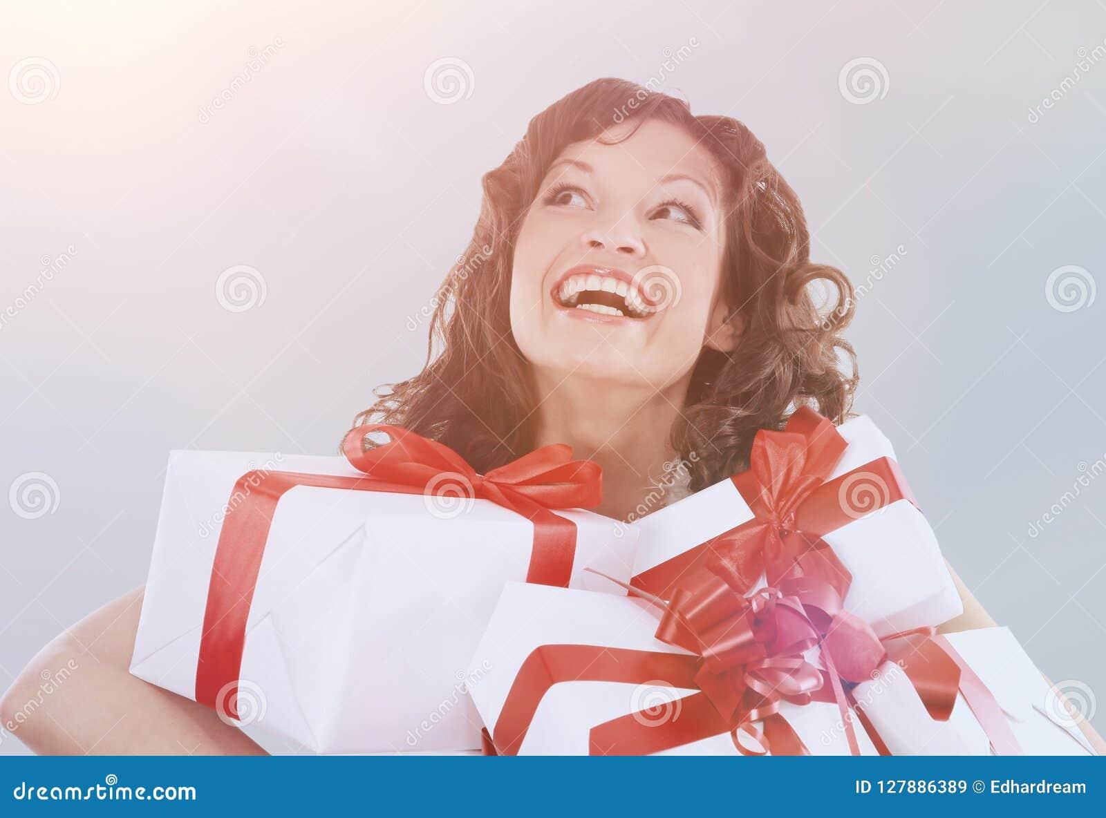 Портрет молодых счастливых усмехаясь подарочных коробок владением женщины