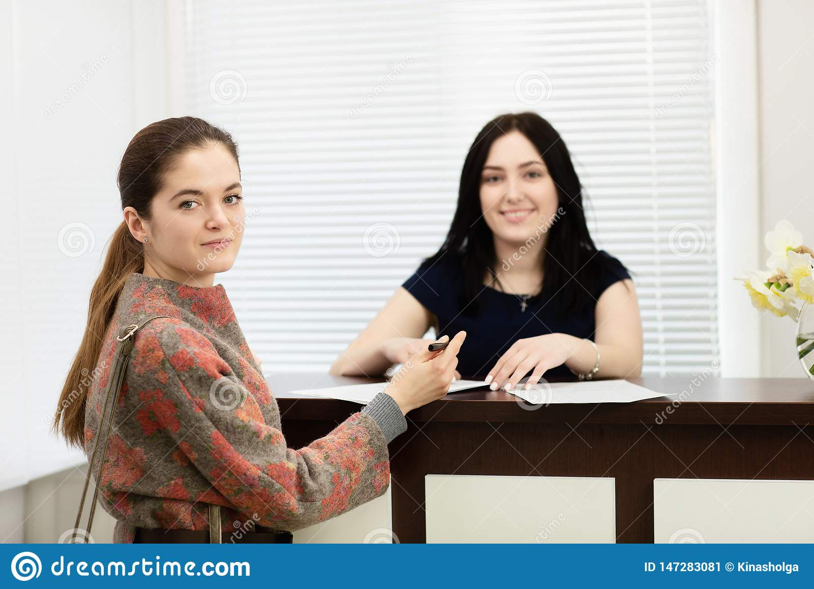 Портрет 2 молодых усмехаясь женщин Администратор зубоврачебной клиники и пациент