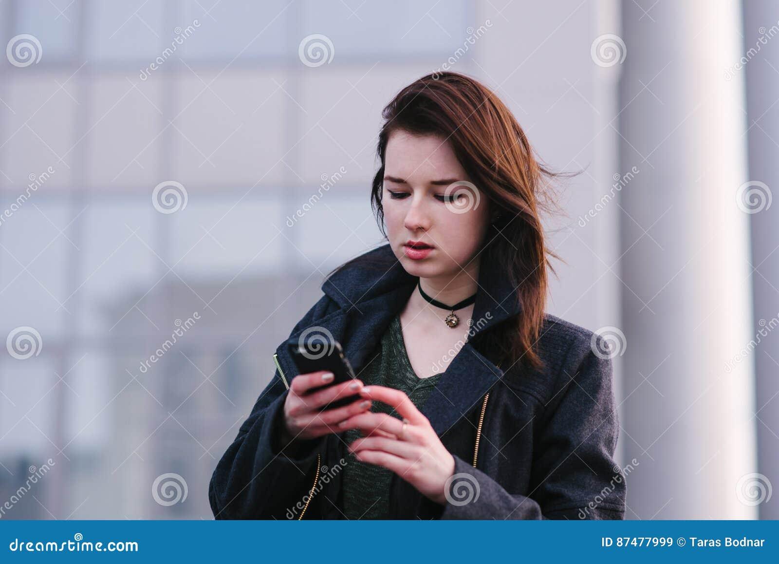 Портрет молодого красивого брюнет женщины в черноте, которая использует мобильный телефон на предпосылке света города