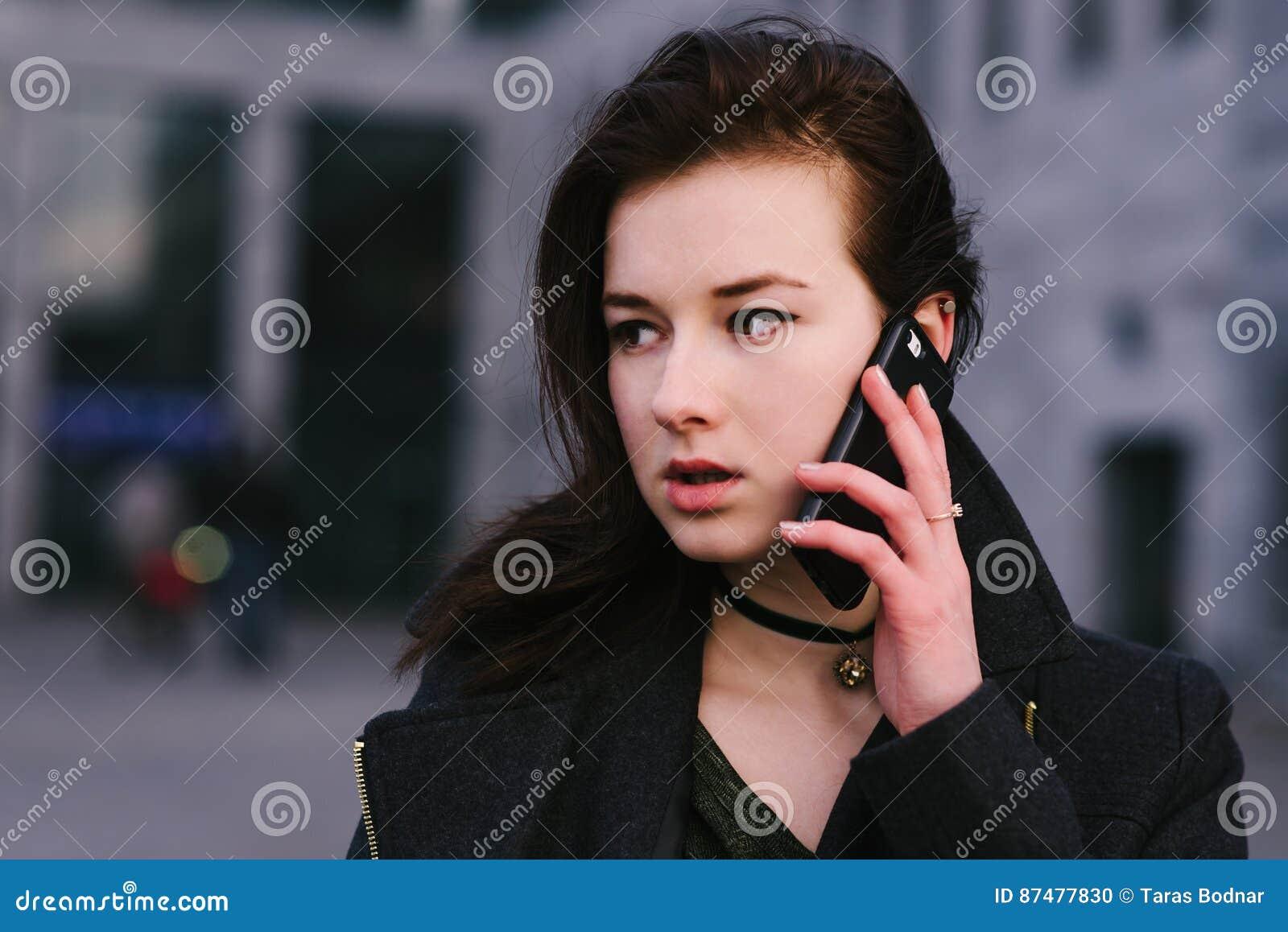 Портрет молодого красивого и серьезного брюнет бизнес-леди говорит на телефоне на городе темную предпосылку