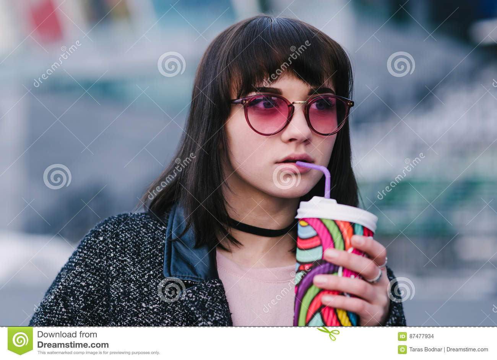 Портрет молодой красивой стильной девушки в розовом битнике стекел который выпивает кофе с красочными чашками