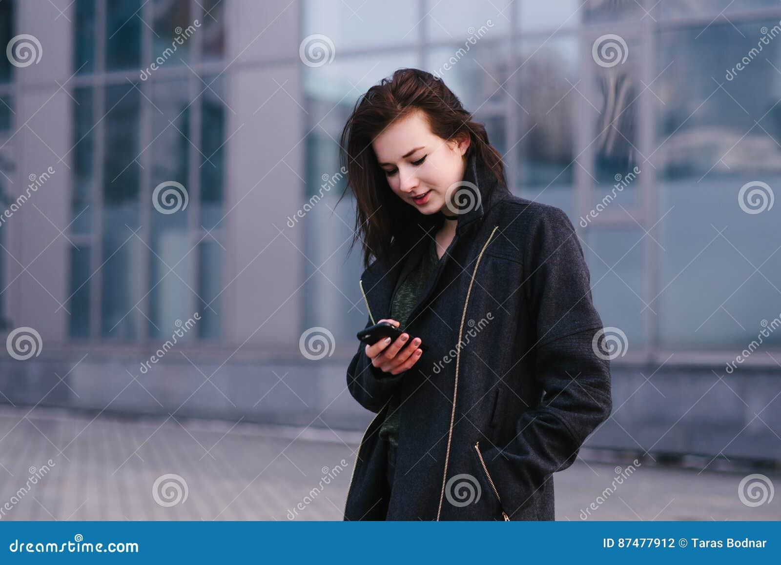 Портрет молодой красивой усмехаясь женщины брюнет которая использует мобильный телефон на предпосылке города