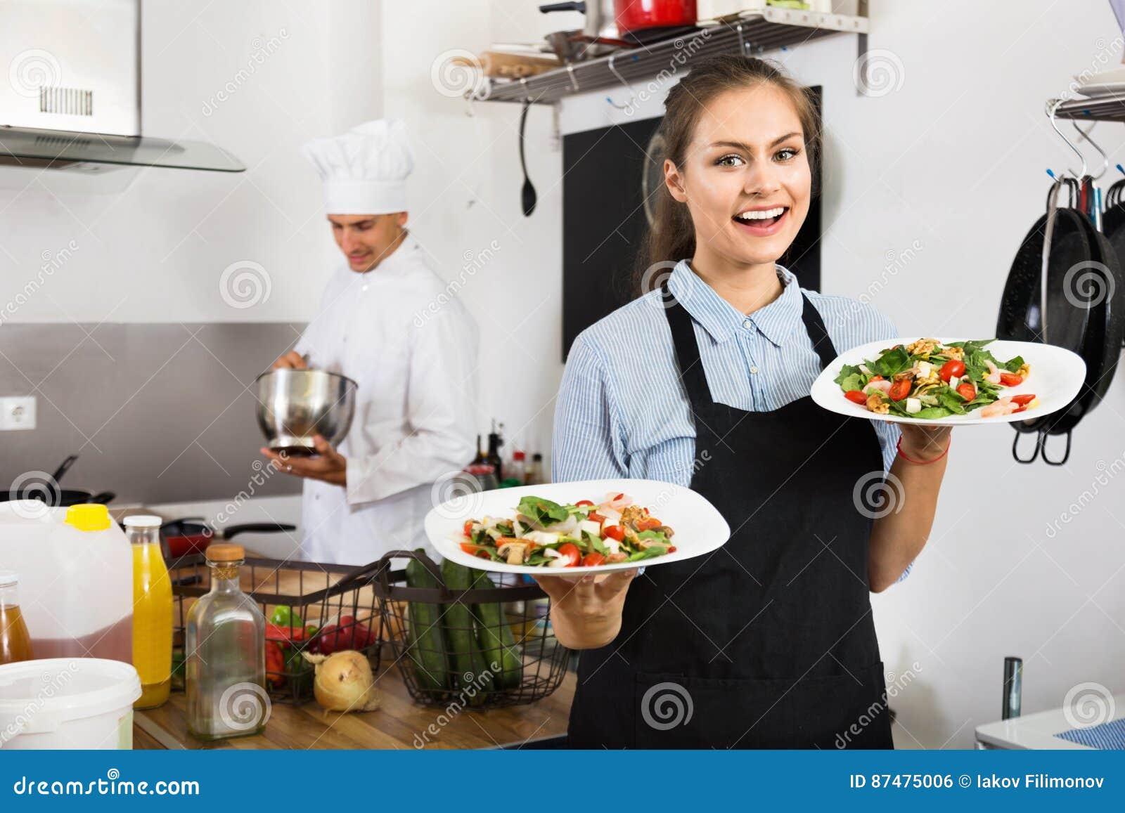 Портрет молодой усмехаясь рисбермы официантки женщины нося