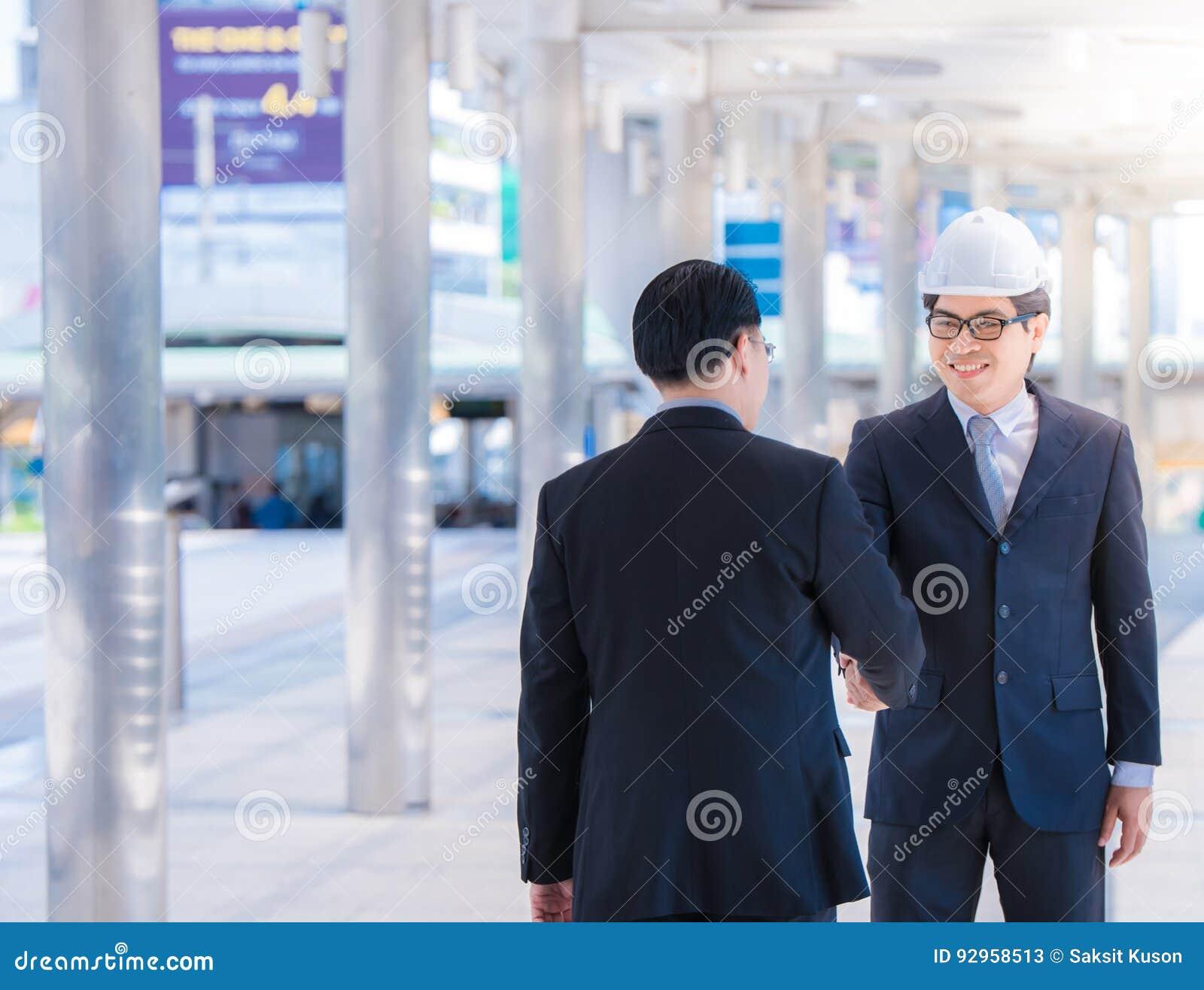Портрет мужского архитектора с защитным шлемом безопасности приветствуя его партнера Построитель молодого человека показывая руко