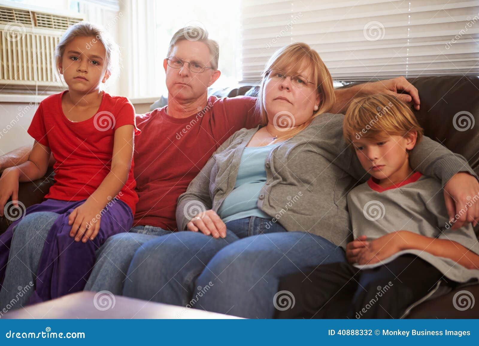 Портрет несчастной семьи сидя на софе совместно