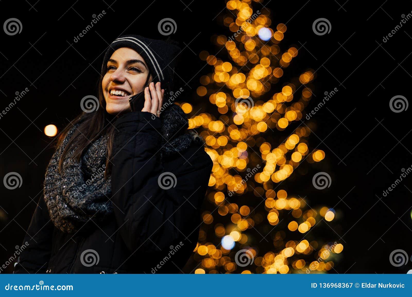 Портрет ночи красивой женщины брюнета используя смартфон во время холодной зимы в парке Утеха зимы зима снежка положения праздник