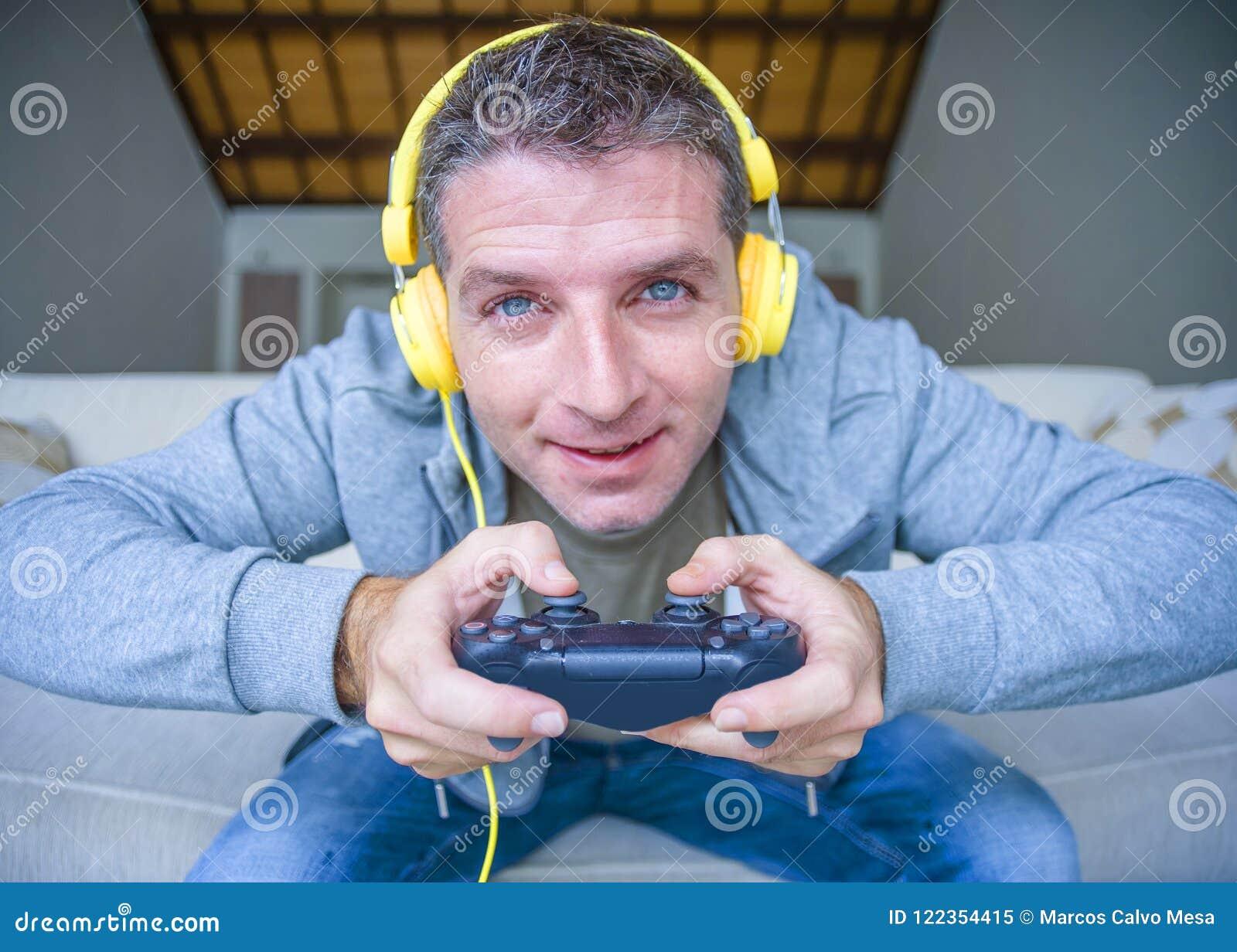Портрет образа жизни молодого счастливого и excited человека gamer при наушники играя видеоигру дома имея потеху на holdi кресла