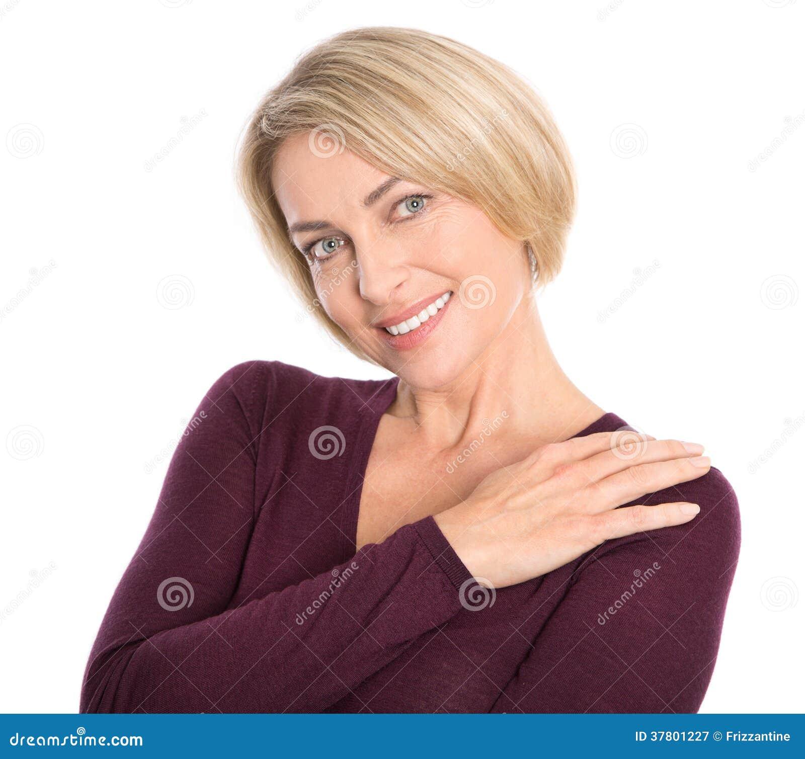 Портрет довольно усмехаясь пожилой женщины изолированной на белизне.