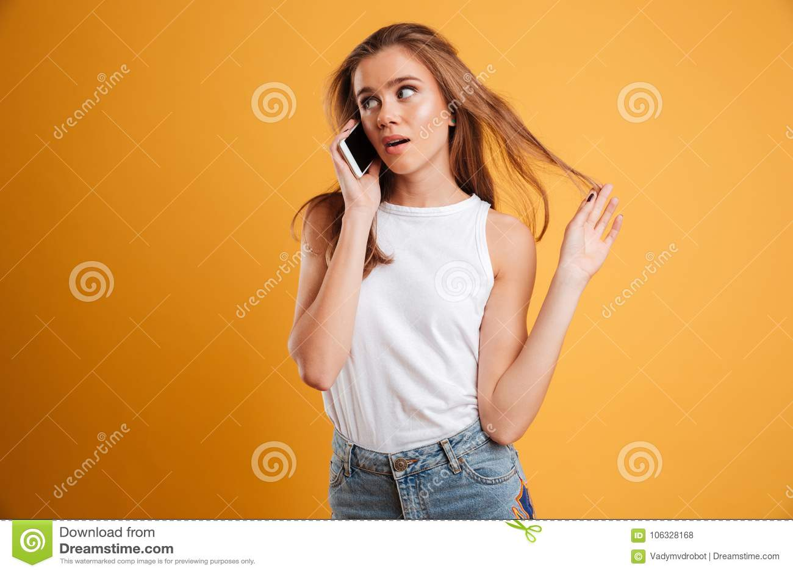 Портрет озадаченной милой девушки говоря на мобильном телефоне