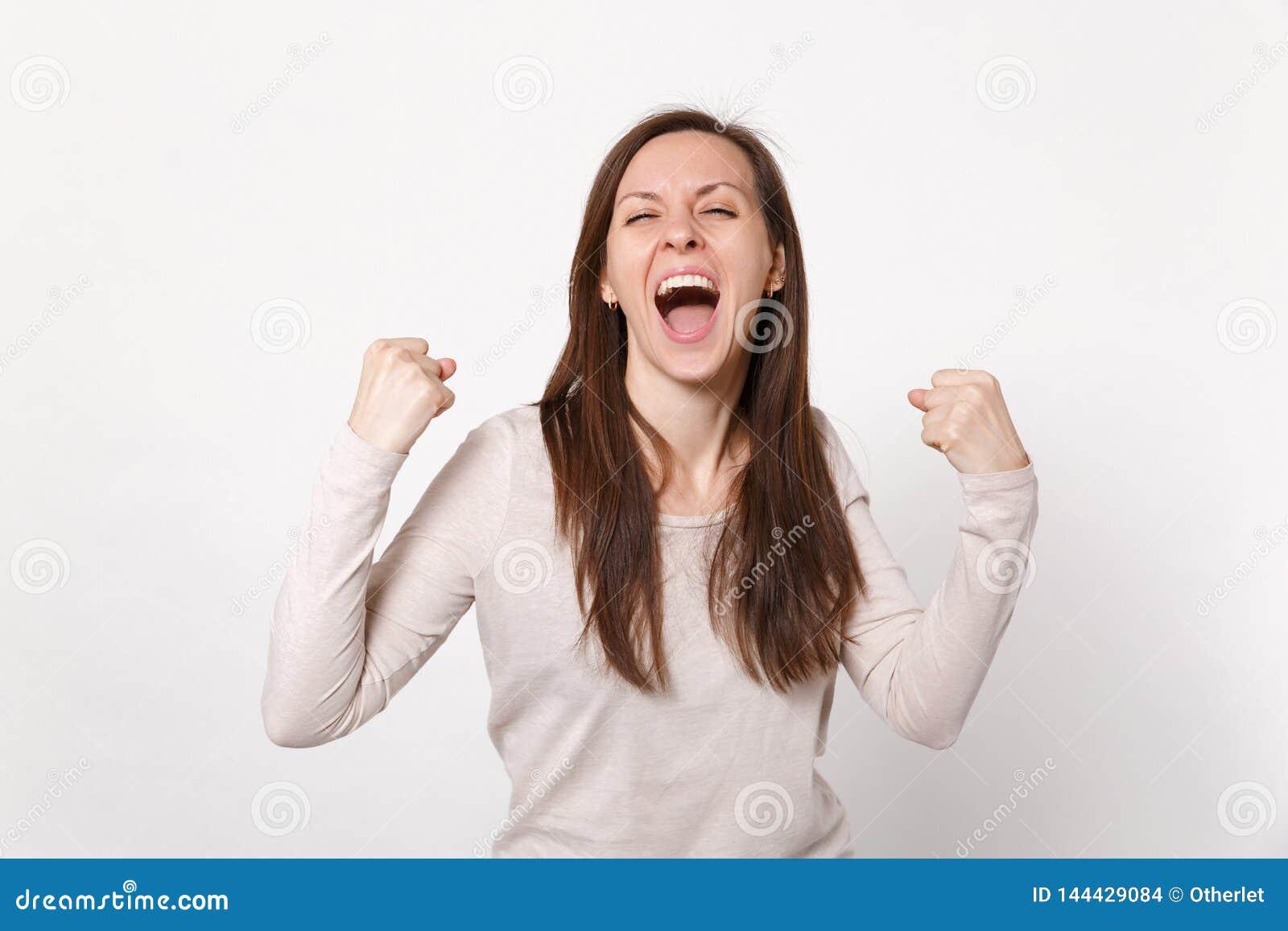 Портрет осчастливленной кричащей молодой женщины в светлых одеждах держа глаза закрыл делать жест победителя изолированные на бел