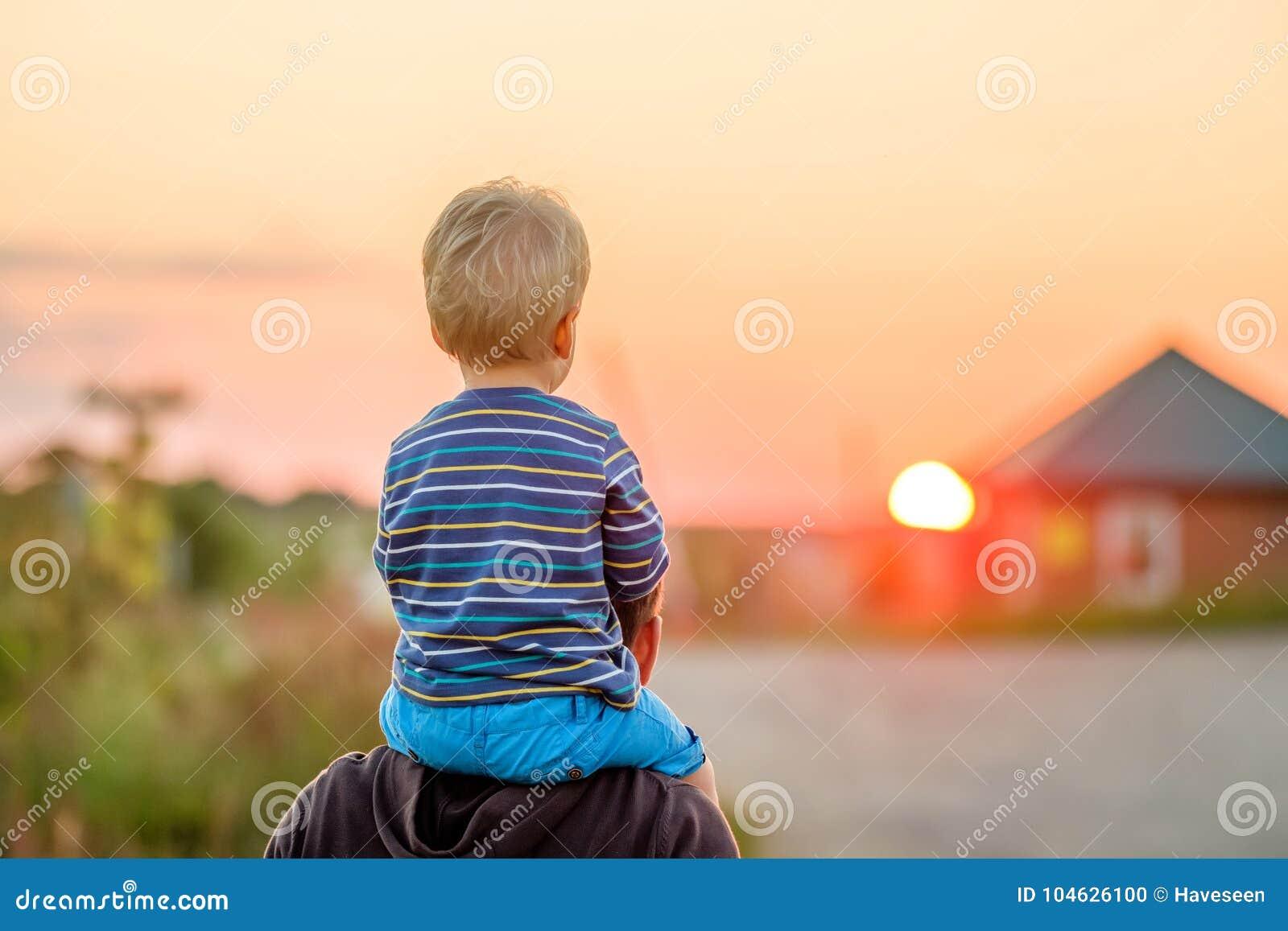 Портрет отца и сына внешний в солнечном свете захода солнца