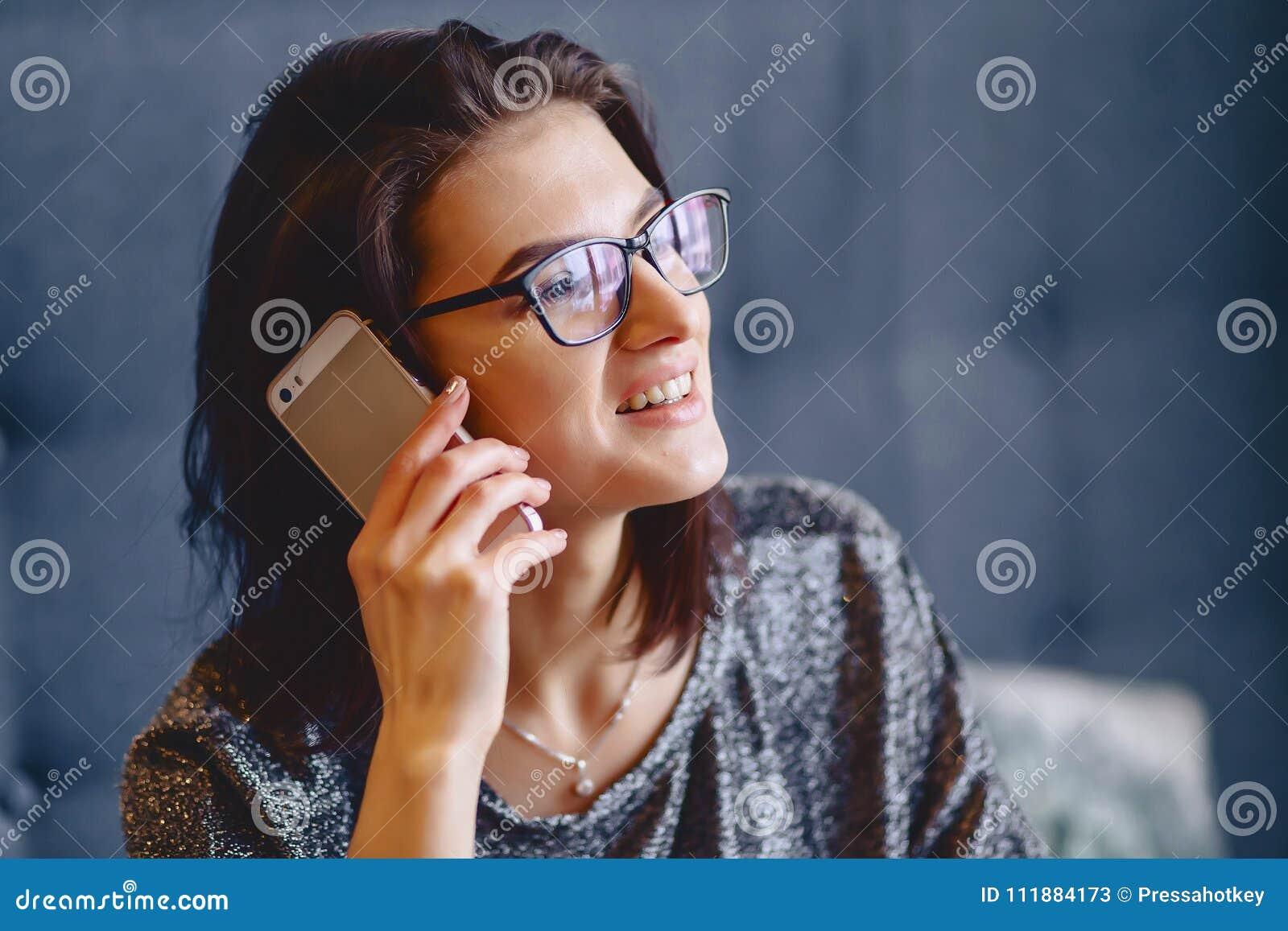 Портрет очаровательной девушки в стеклах с телефоном