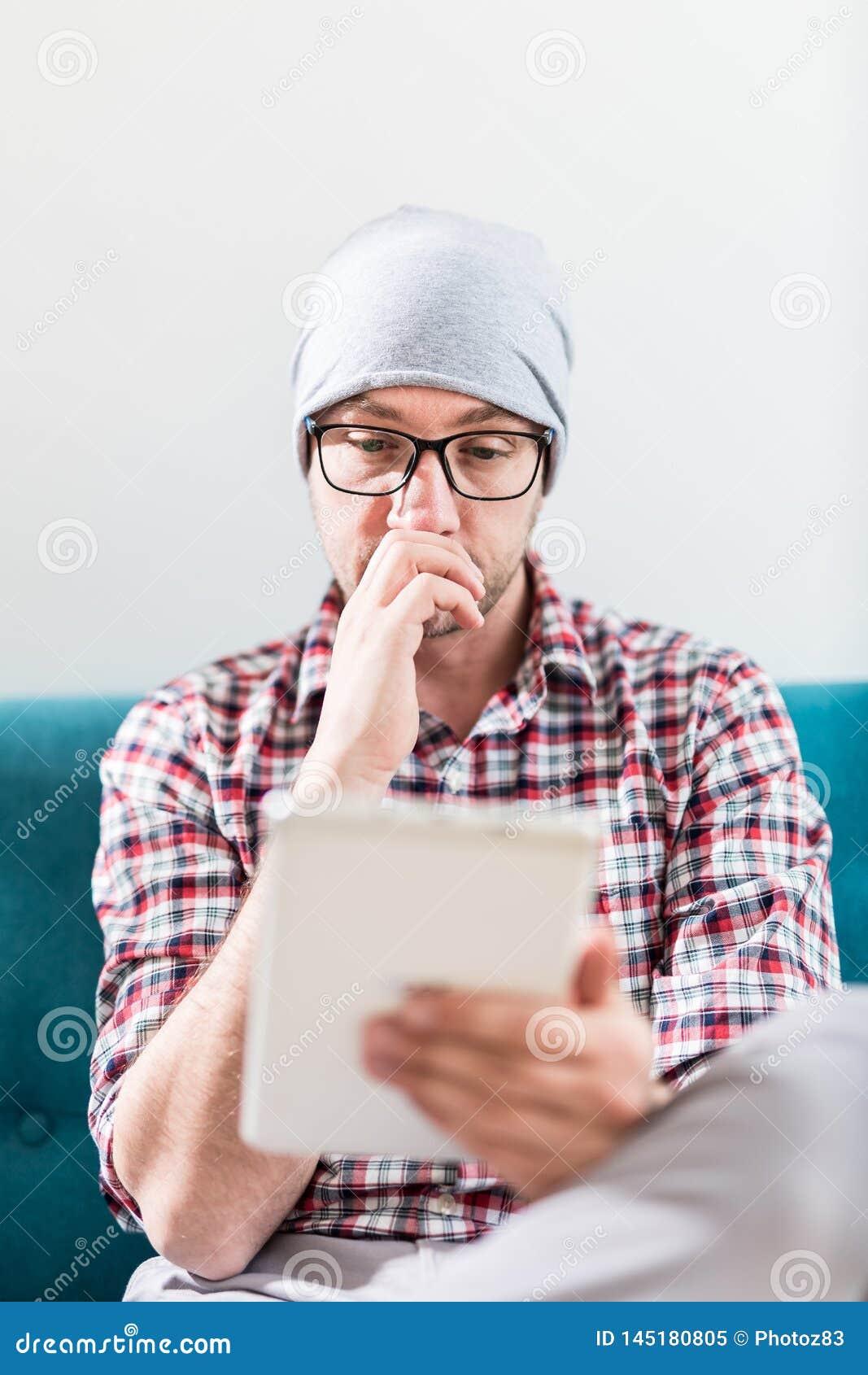 Портрет парня хипстера сидя в софе и смотря цифровой планшет