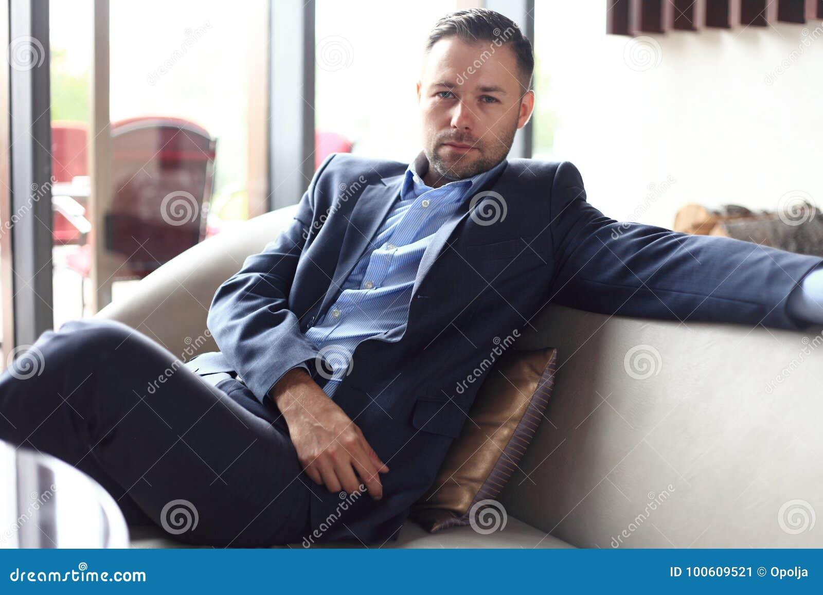 Портрет положительного молодого бизнесмена сидя в современной корпоративной окружающей среде, смотря камеру
