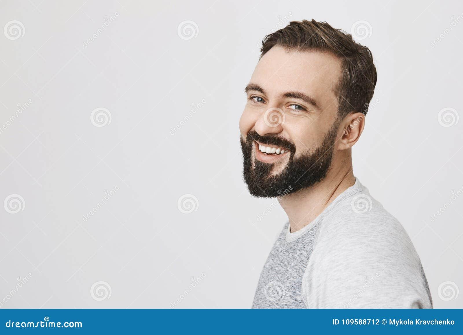 Портрет привлекательного молодого взрослого человека с бородой и усиком окантовал камеру, выражая счастье, пока стоящ