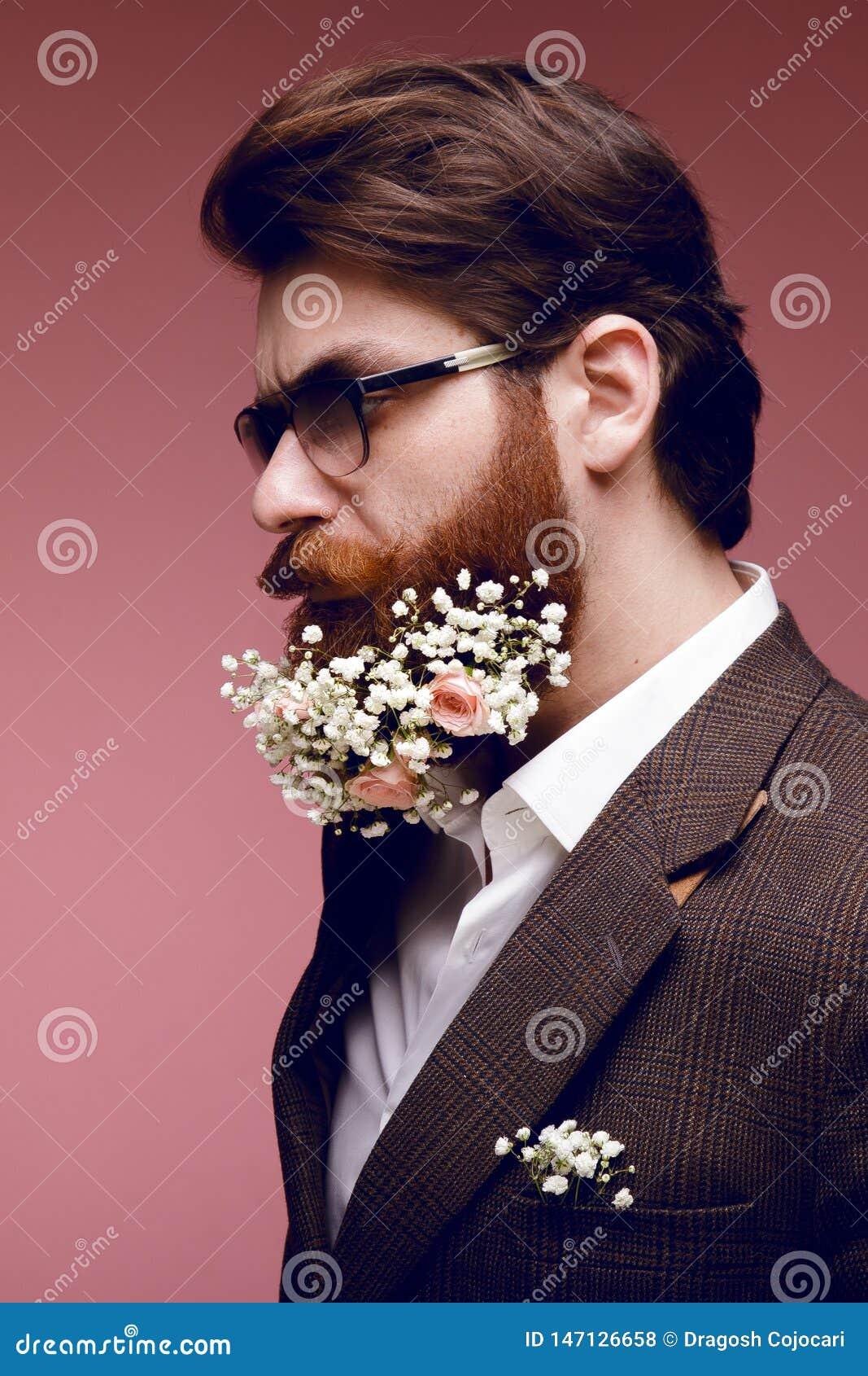 Портрет профиля модного бородатого человека с цветками в бороде, изолированный на темной розовой предпосылке