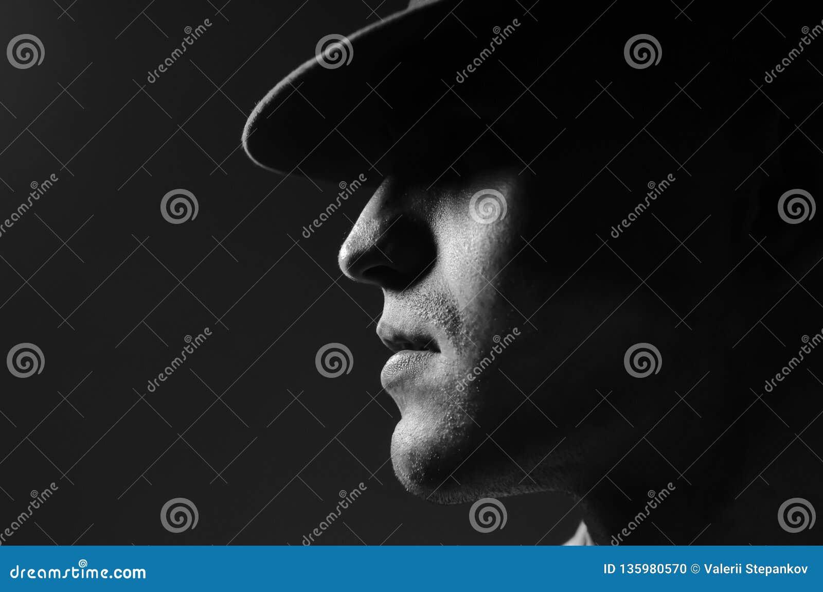 Портрет профиля молодого человека в положении шляпы над темным - серая предпосылка конец вверх классицистический тип Экземпляр-ко