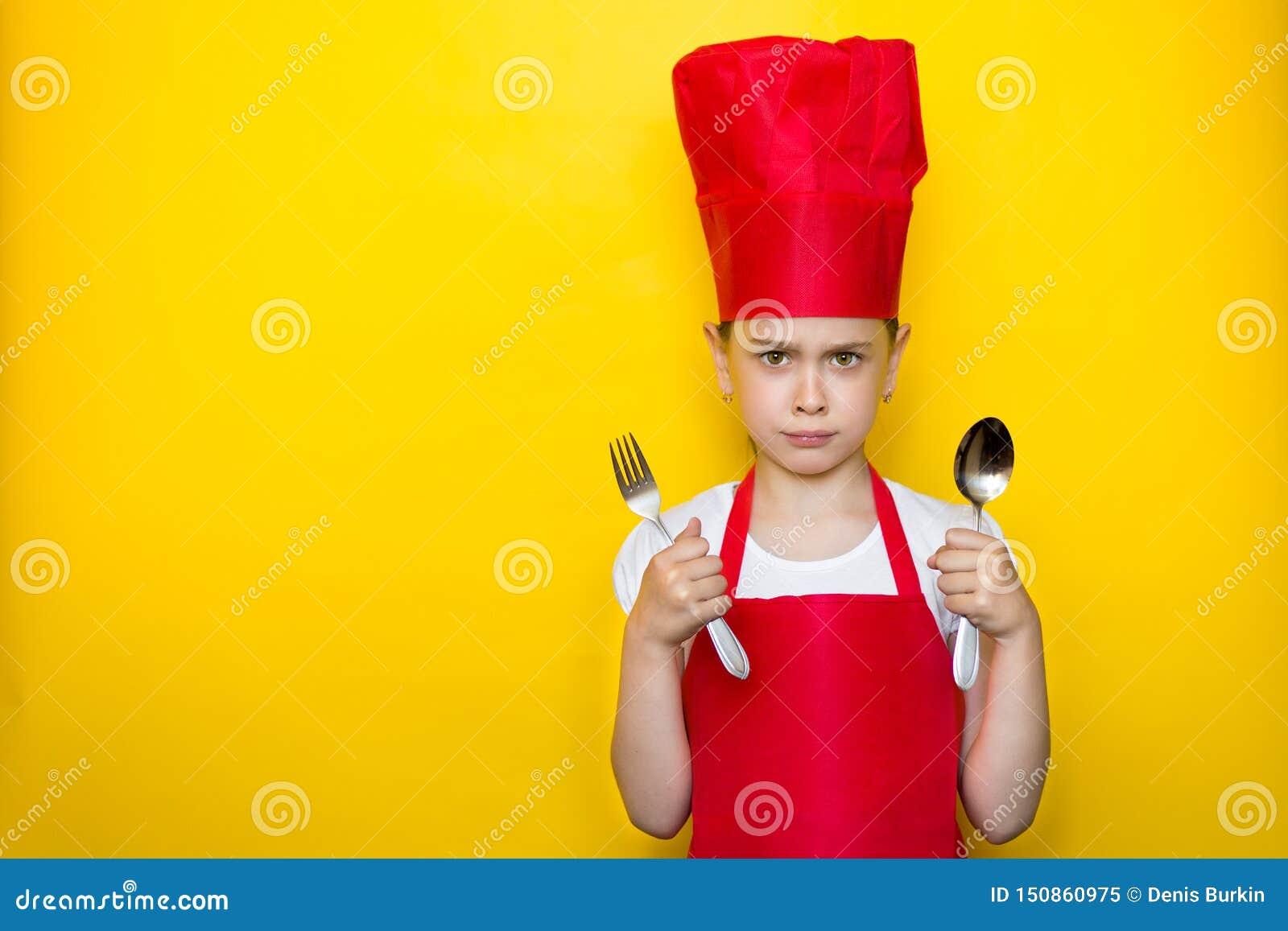Портрет расстроенной маленькой девочки в костюме красного шеф-повара держа ложку и вилку на желтой предпосылке с космосом экземпл