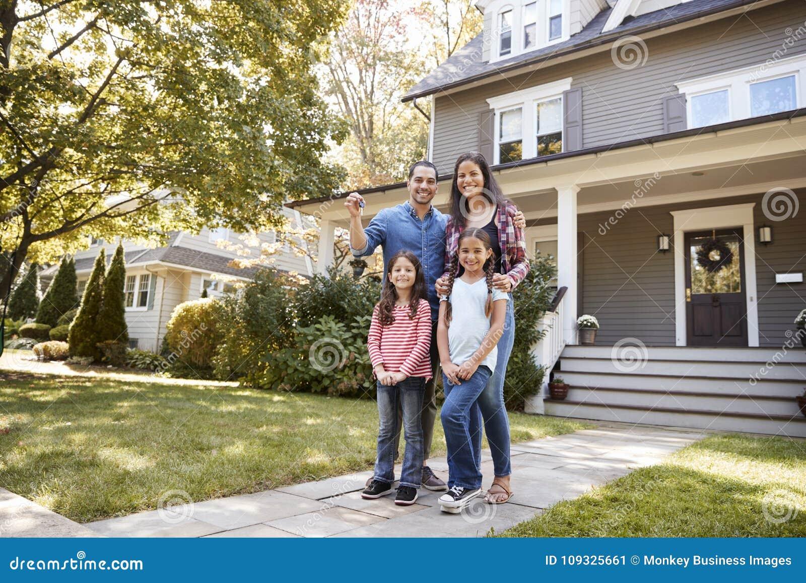 Портрет семьи держа ключи к новому дому на двигать в день