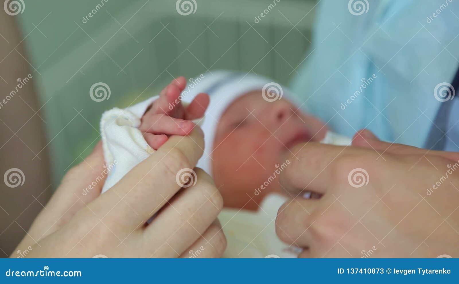 Портрет семьи конца-вверх меньших милых рук младенца в руках родителя сток-видео
