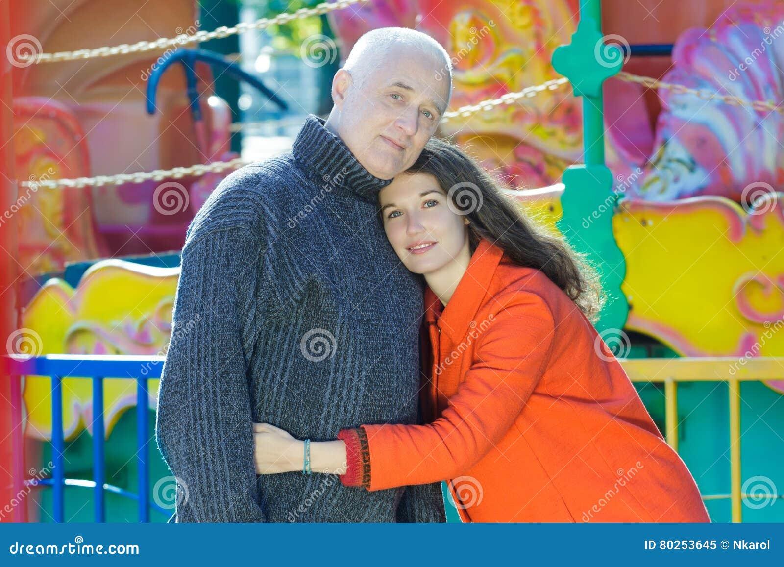 Портрет семьи парка атракционов внешний обнимать взрослую дочь и старший отца
