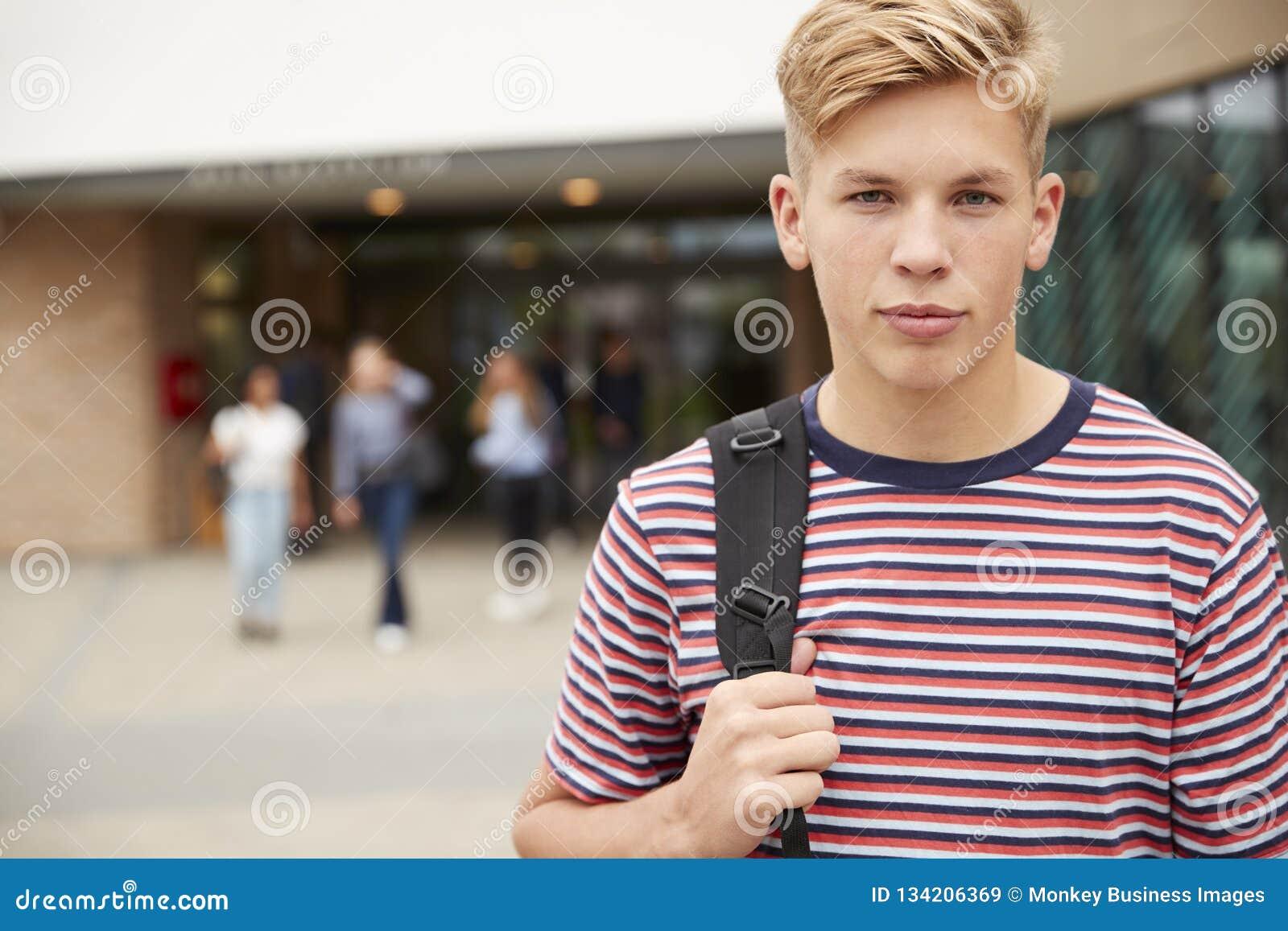 Портрет серьезного мужского студента средней школы вне здания коллежа с другими подростковыми студентами в предпосылке