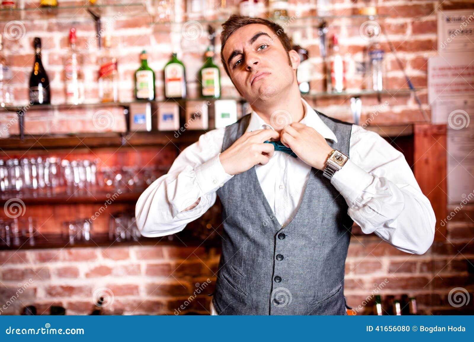 Портрет сердитого и усиленного бармена с bowtie за баром