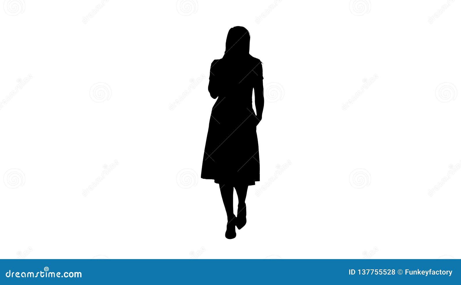 Портрет силуэта идти счастливая молодая женщина говоря на мобильном телефоне и усмехаться