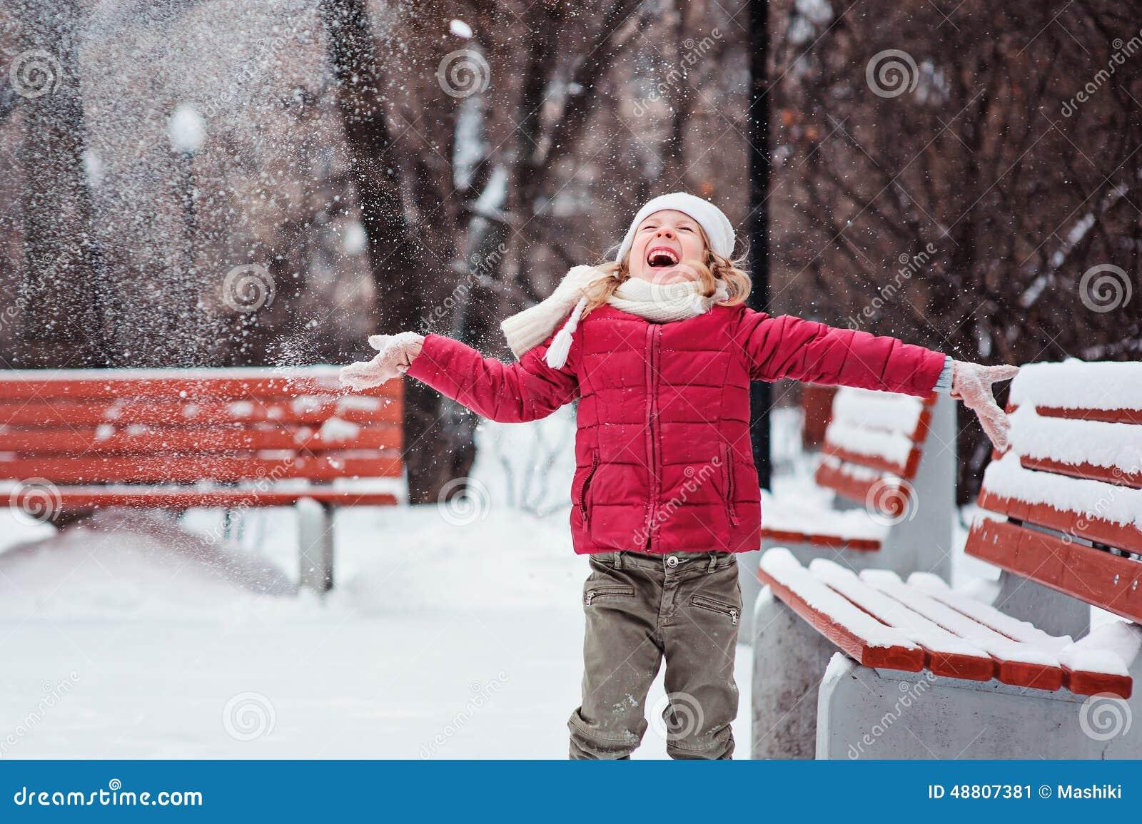 Портрет снега счастливой девушки ребенка бросая на прогулке в парке зимы