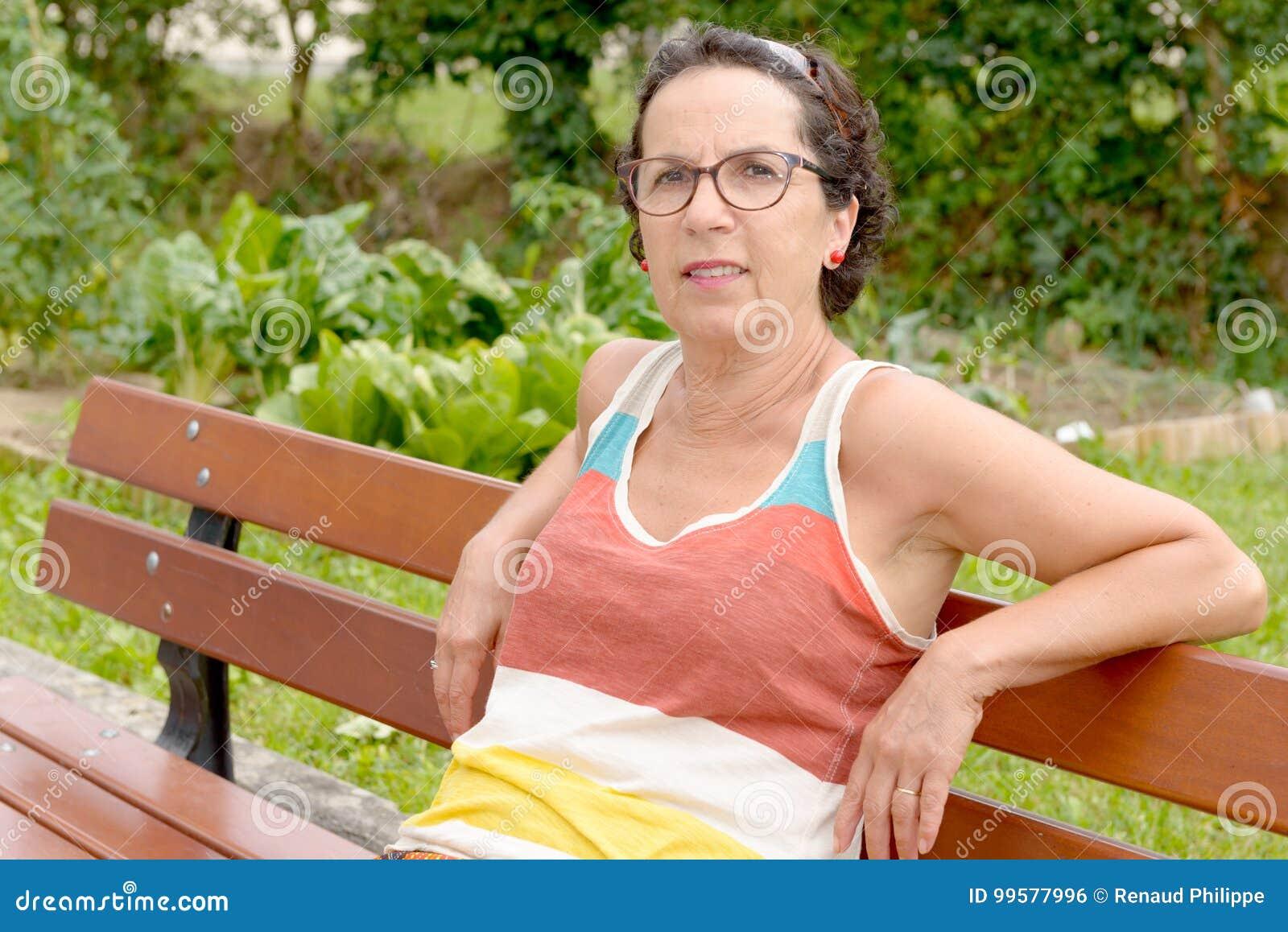 Портрет средн-постаретой женщины с eyeglasses, outdoo брюнет