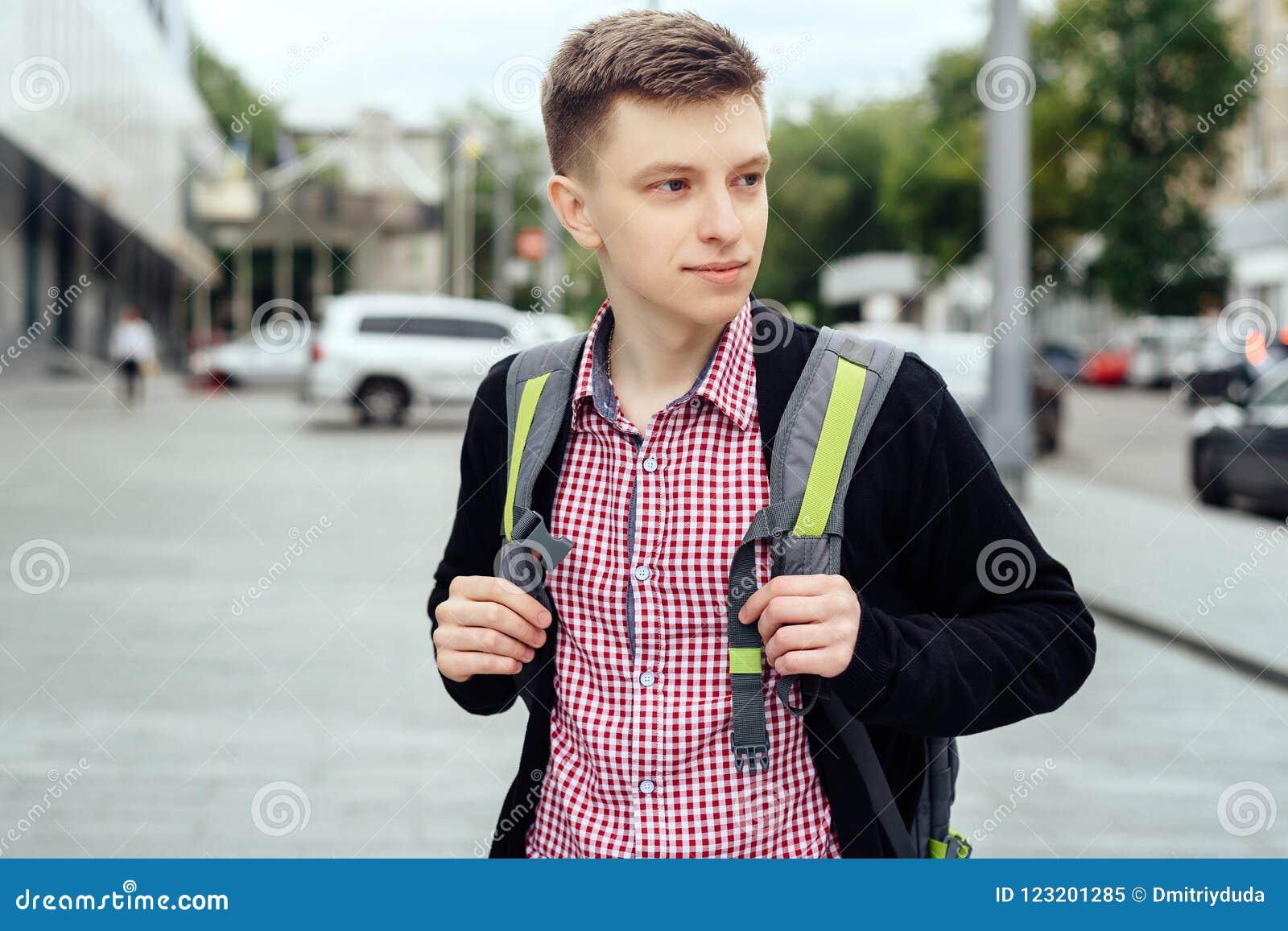 Портрет стильного молодого человека в рубашке и куртке шотландки с рюкзаком идя в город outdoors Перемещение студента