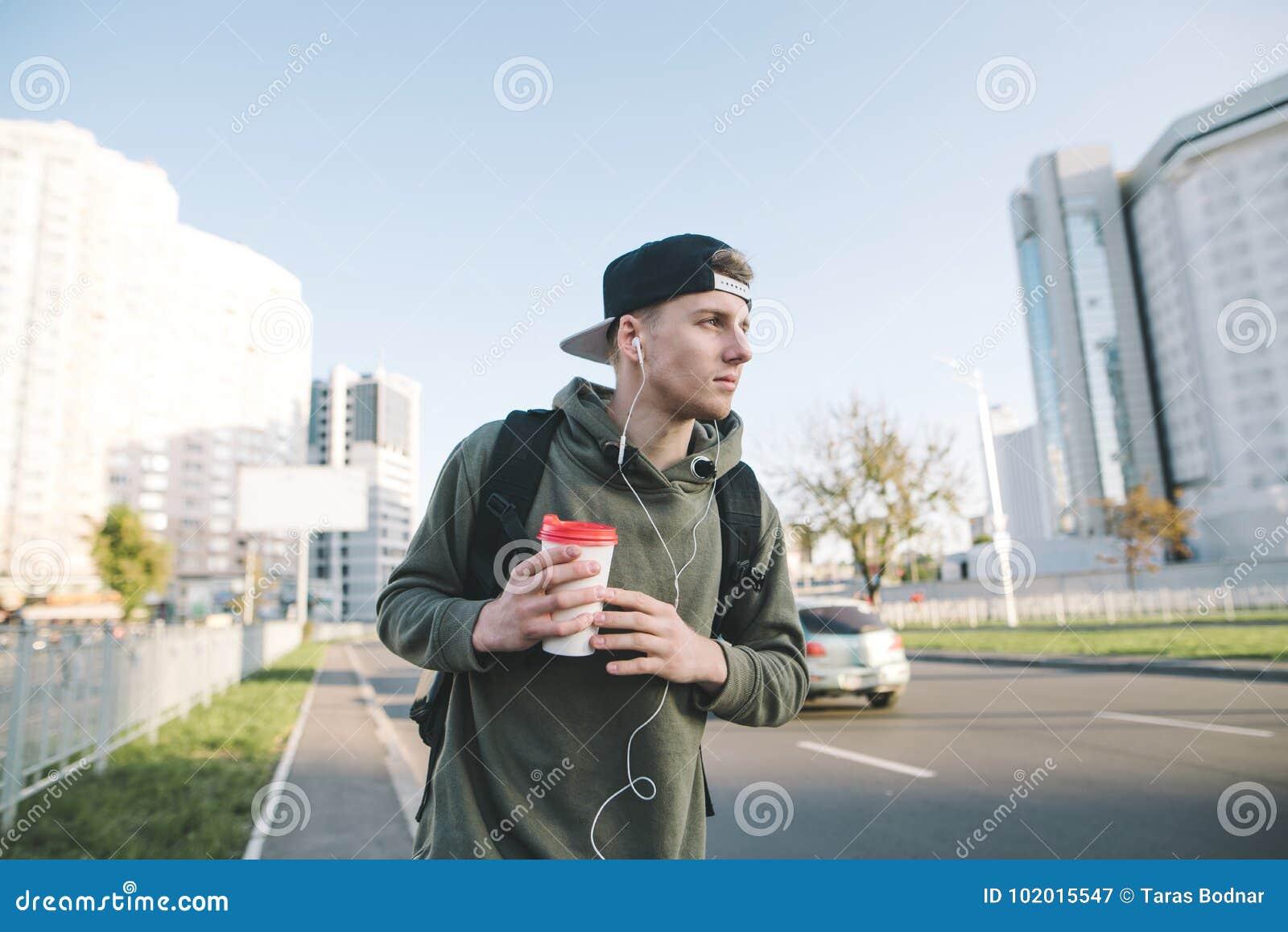 Портрет стильного молодого человека идя вниз с улицы его города с чашкой кофе в его руках и слушая к музыке в th