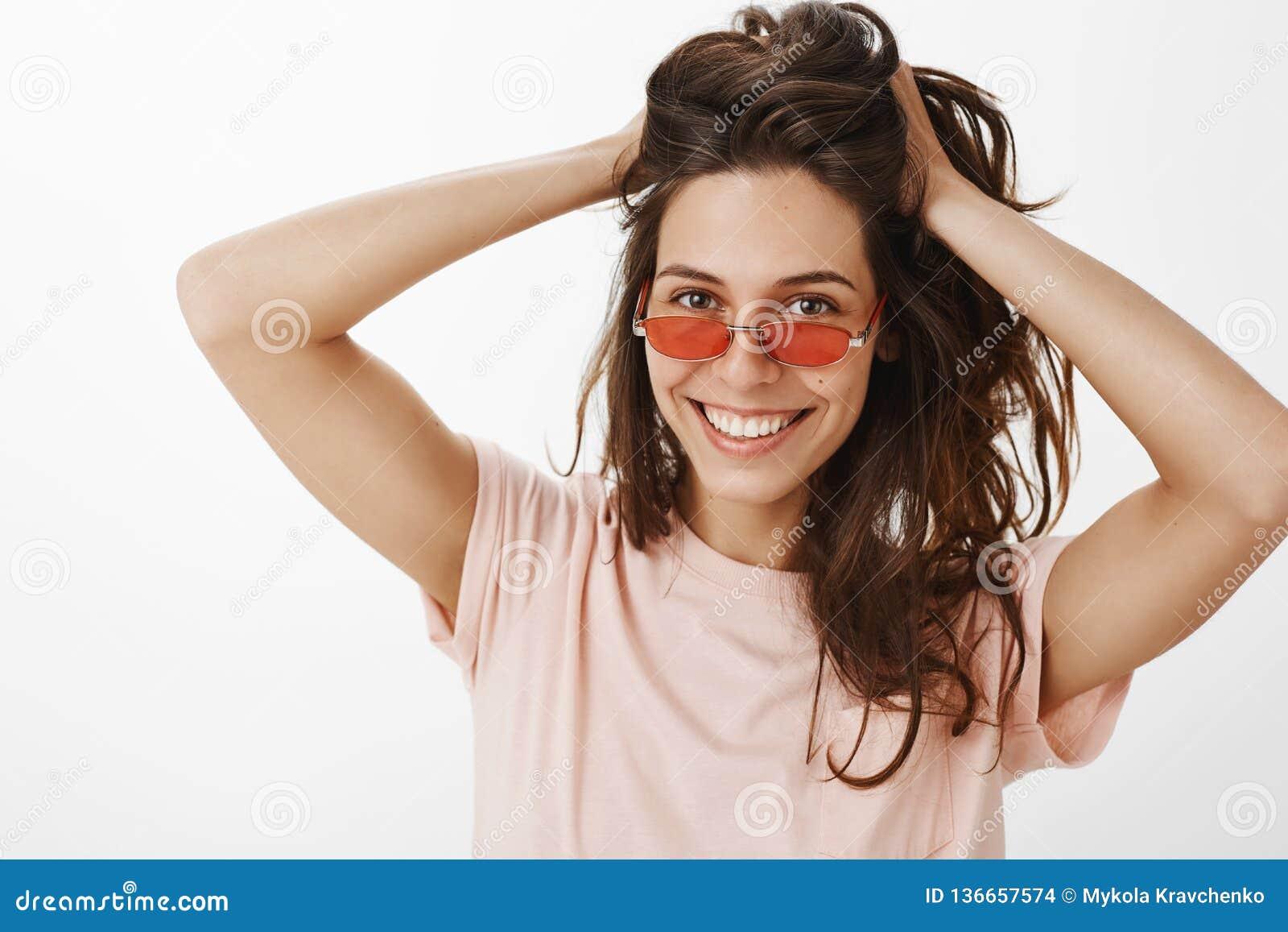 Портрет стильной жизнерадостной девушки партии в красных солнечных очках касаясь и играя с красивыми естественными волосами расче