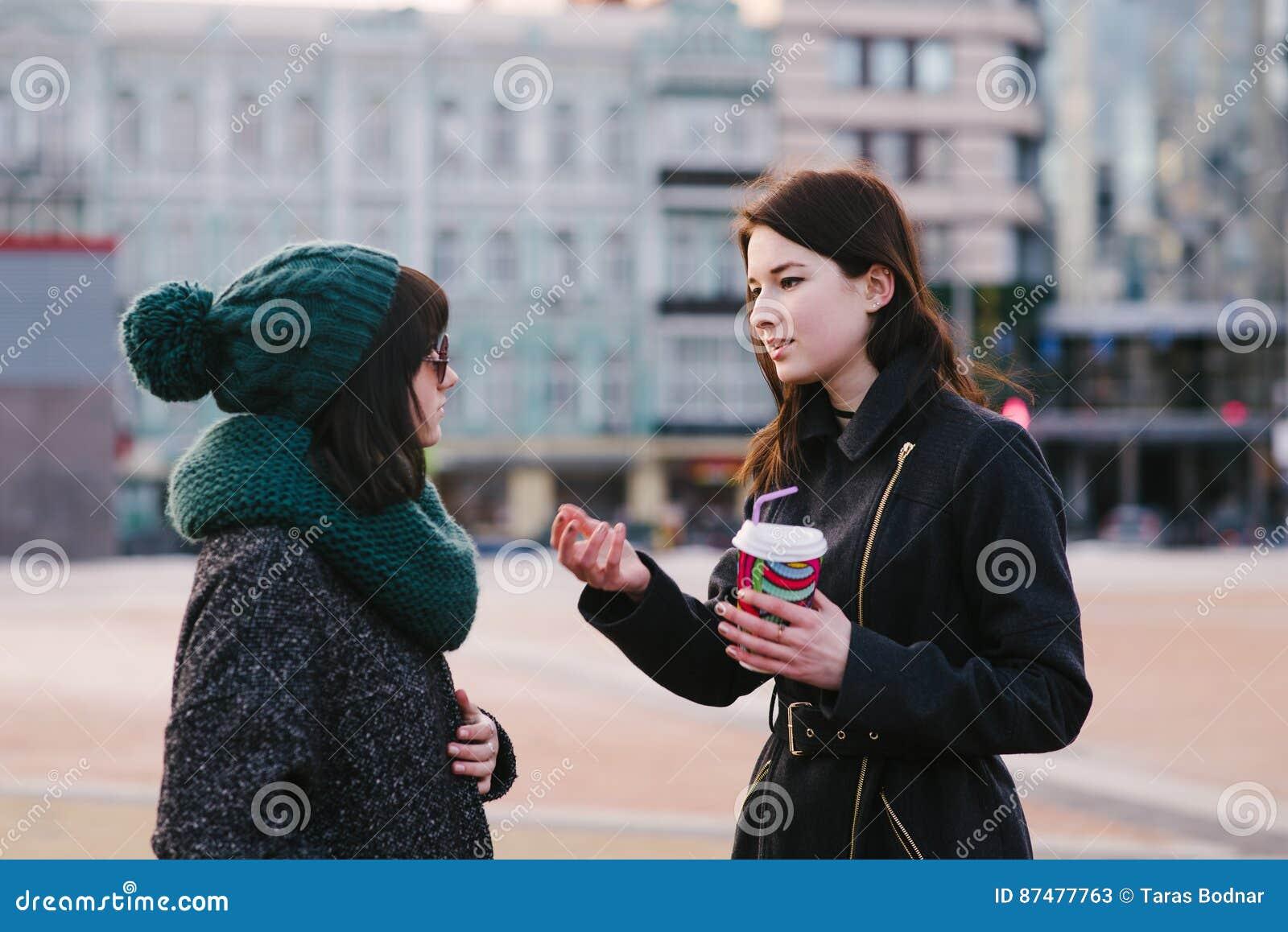 Портрет 2 стильного и красивые подруги стоя на улице и говоря середине города