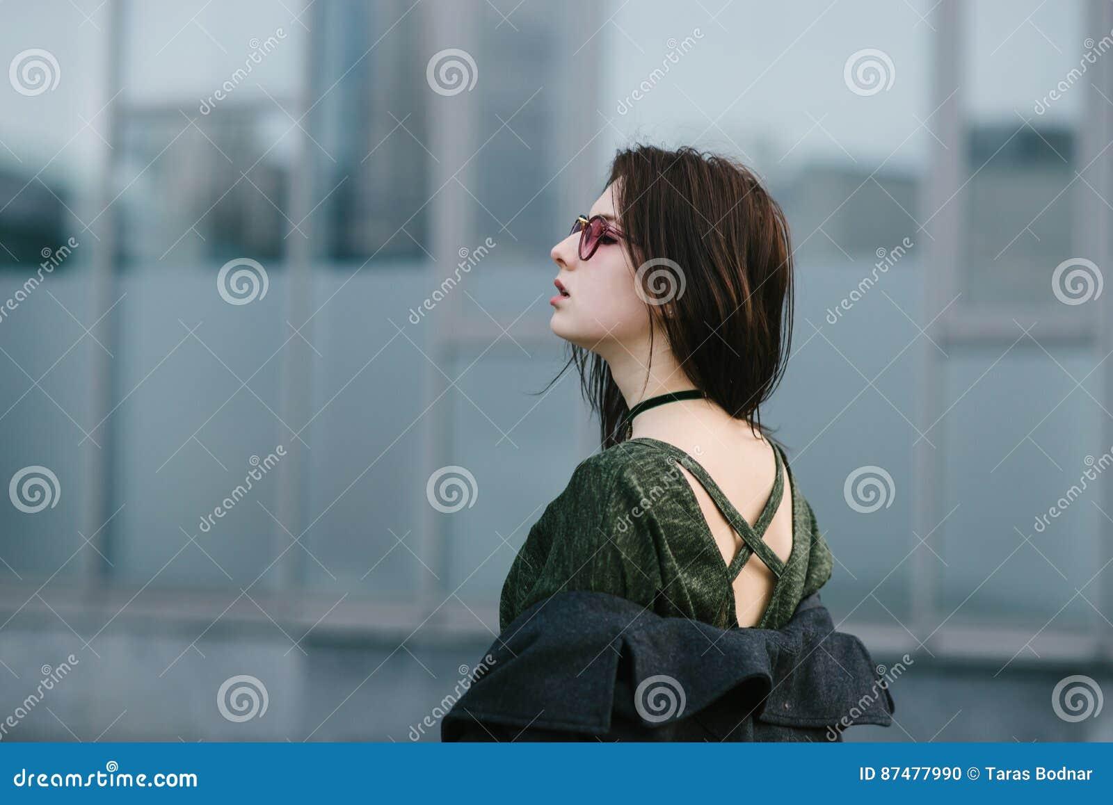 Портрет стильно одел девушку брюнет в стеклах которая показывает их задние части на предпосылке запачканной серым цветом