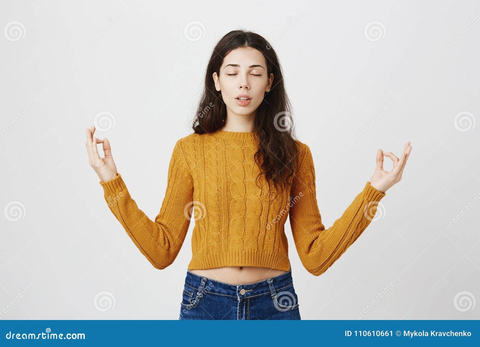 Портрет студии выразительных детенышей уменьшает женский размышлять, распространяющ руки с жестом Дзэн, был спокоен пока стоящ
