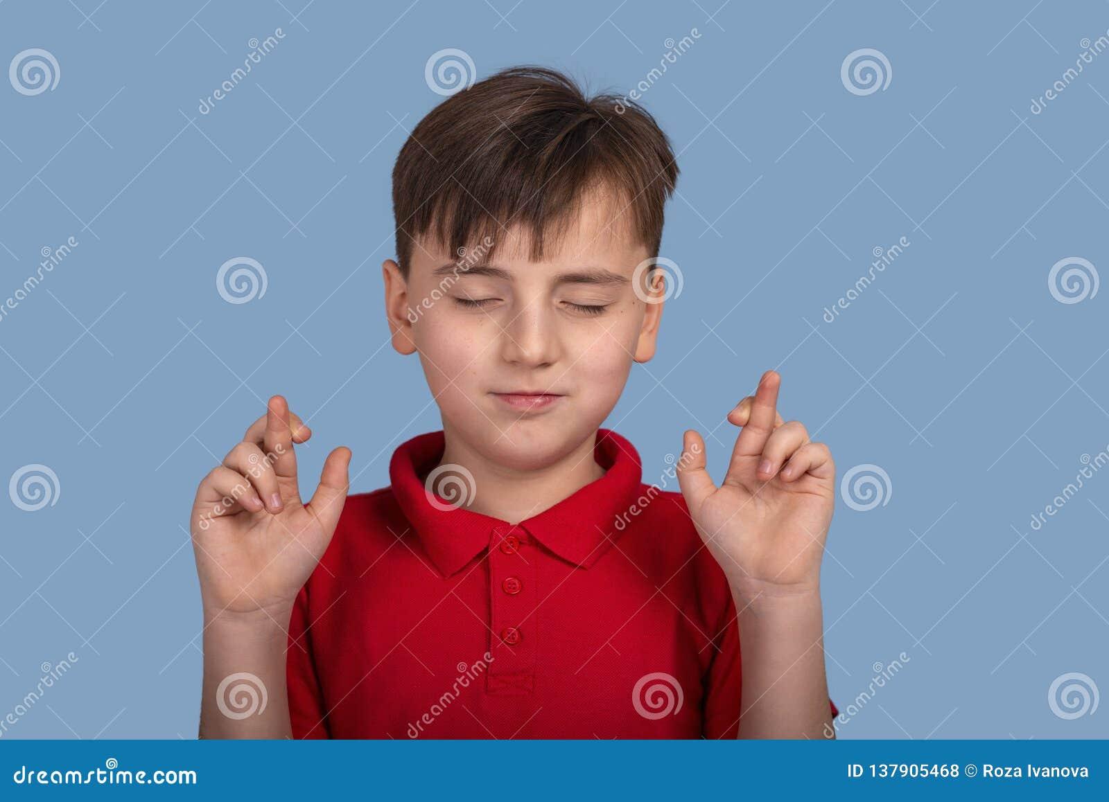 Портрет студии a мальчика с закрытыми глазами предлагая желание и показывая руки с пересеченными пальцами на голубой предпосылке